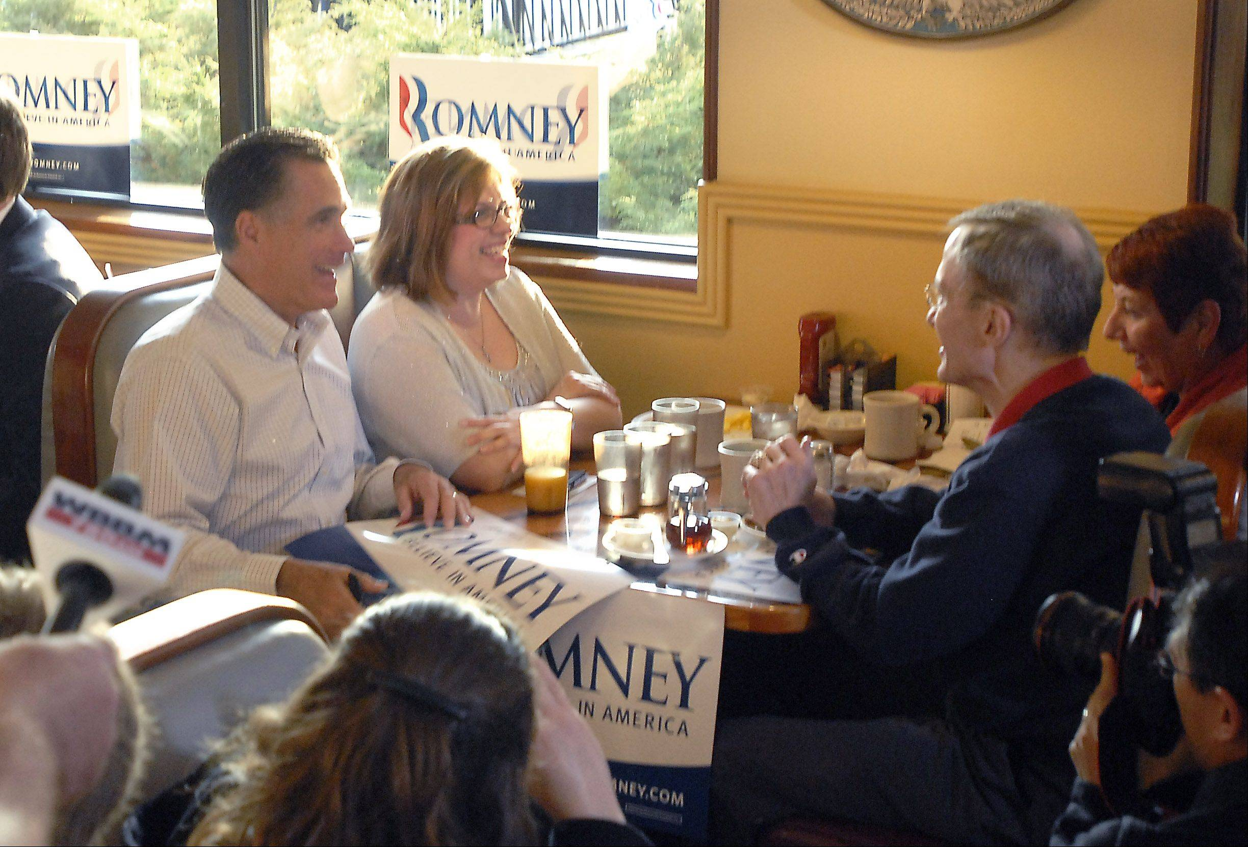 Republican presidential candidate Mitt Romney sits down with supporters early Friday morning at a restaurant in Rosemont.