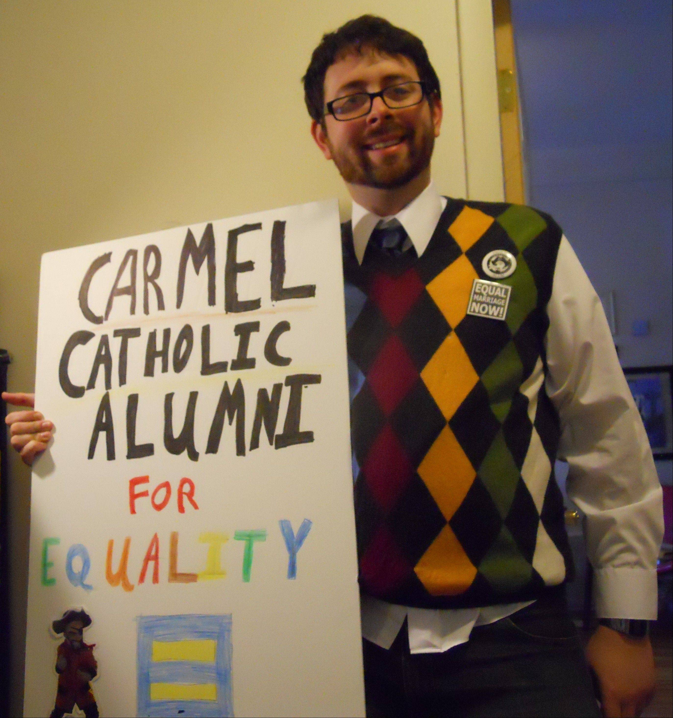 Matt Muchowski, from the Carmel Catholic Alumni Against Rick Santorum group, poses with one of the signs he'll have at Friday's protest when the Republican presidential candidate comes to Christian Liberty Academy in Arlington Heights. Santorum graduated from Carmel Catholic High School in Mundelein in 1976; Muchowski in 2002.
