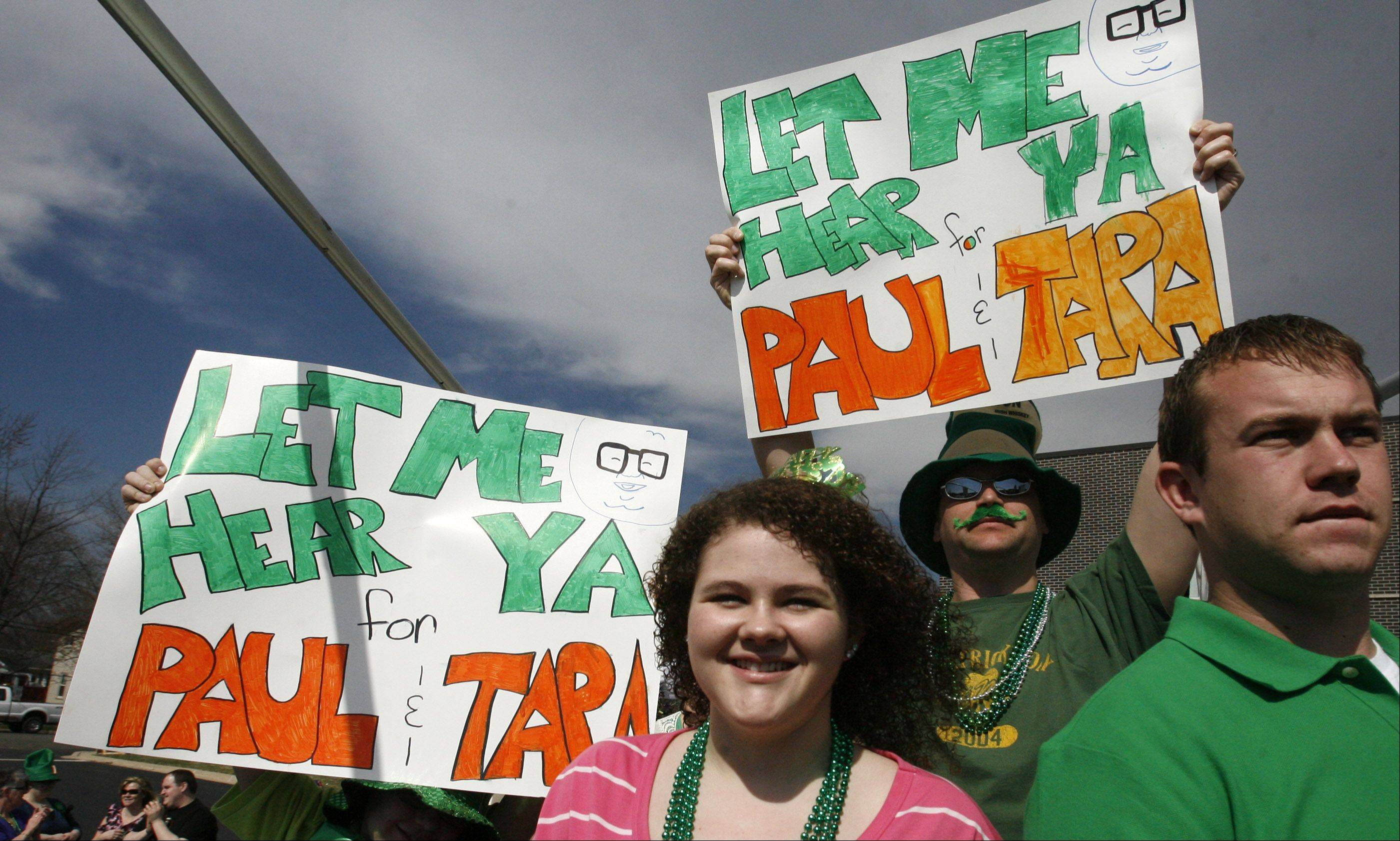 Friends hold up signs while riding on Tara Teschky and Paul Quinn's wedding float during the Lake Villa St. Patrick's Day parade on Saturday.