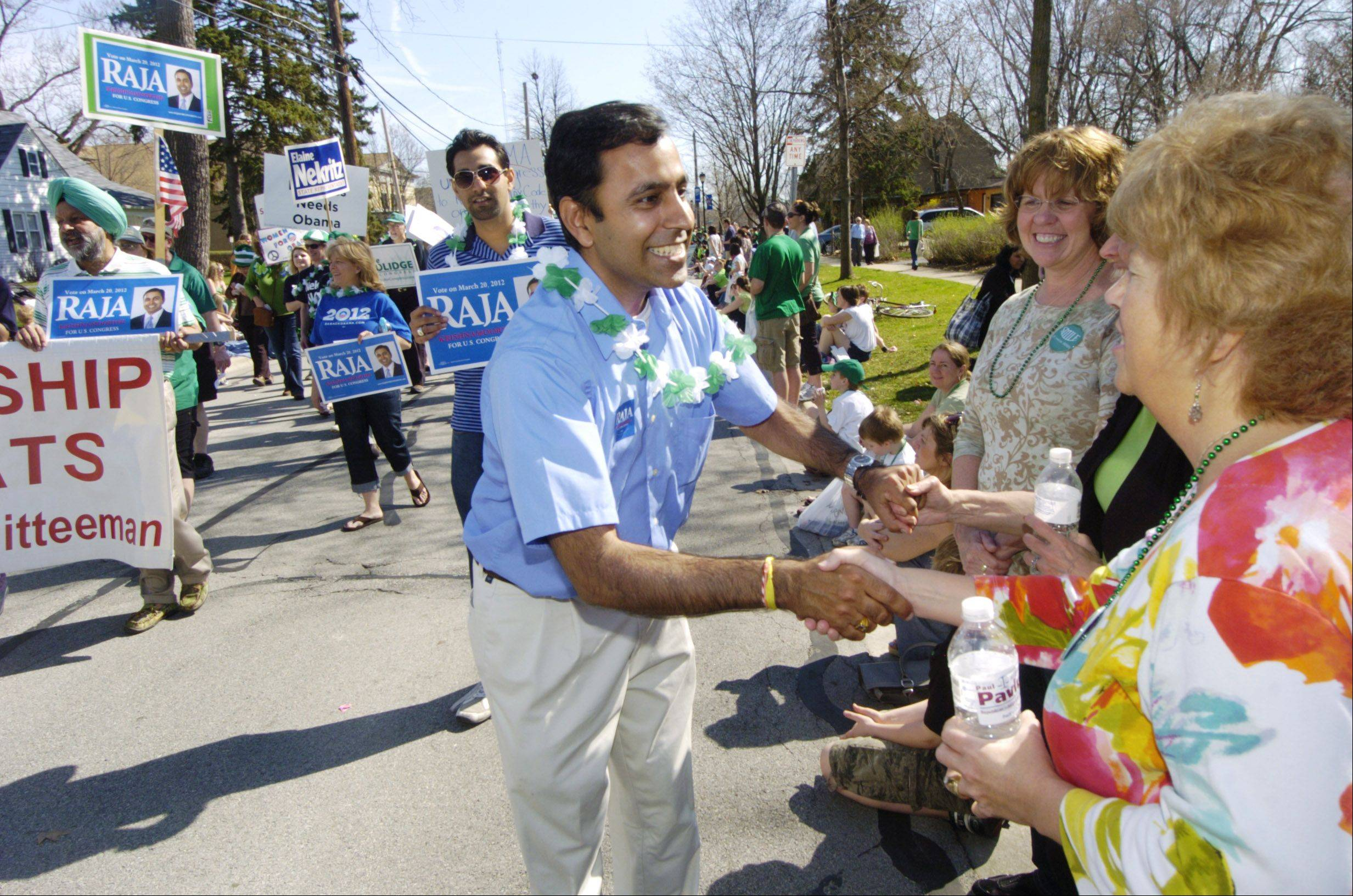 Raja Krishnamoorthi, Democratic candidate in the 8th Congressional District, greets members of the crowd lining Wood Street on Saturday during the Palatine St. Patrick's Day Parade.
