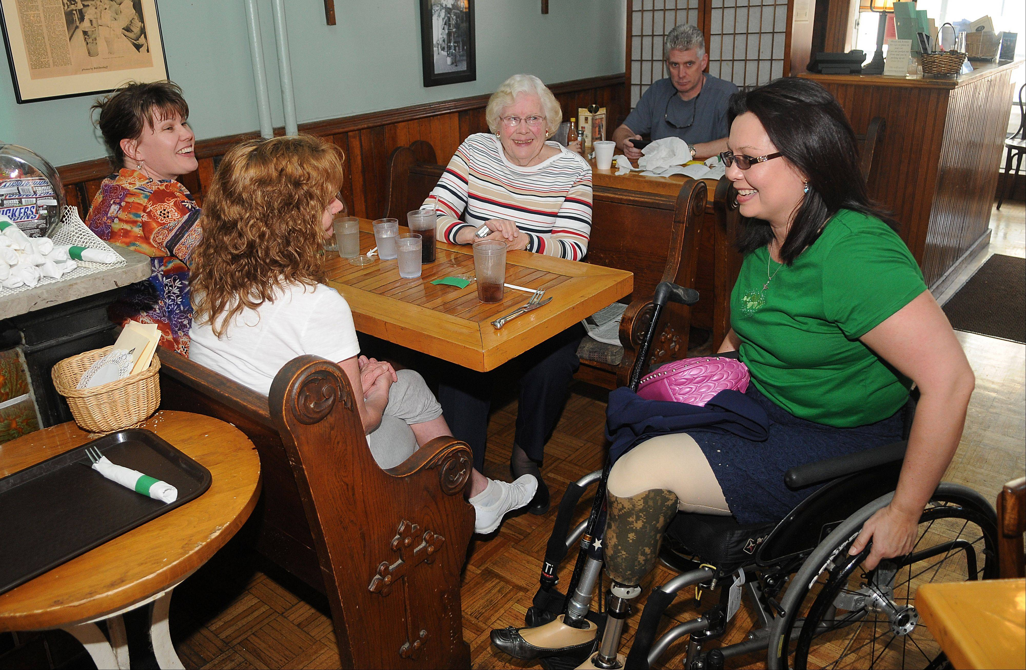 "Tammy Duckworth, candidate for the 8th Congressional District, chats with Julie Thompson of Carpentersville, Ruth Allen of Elgin, and Lori Allen of Algonquin on Saturday while stopping in at Al's Cafe in Elgin. The ladies recognized Duckworth right away, with Ruth Allen saying she admired Duckworth for her ""courage and convictions."""