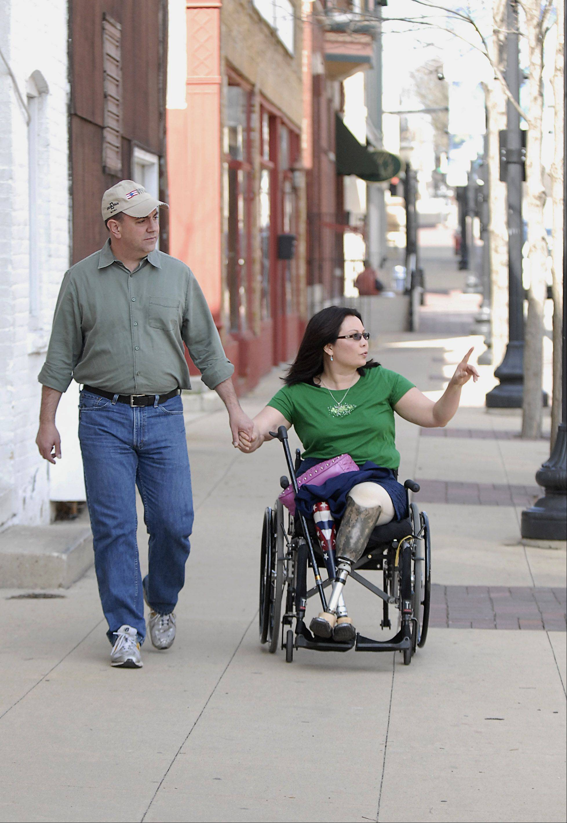 Tammy Duckworth and her husband, Bryan, stroll down Spring Street on Saturday while visiting Elgin to campaign for votes in the 8th Congressional District Democratic primary.