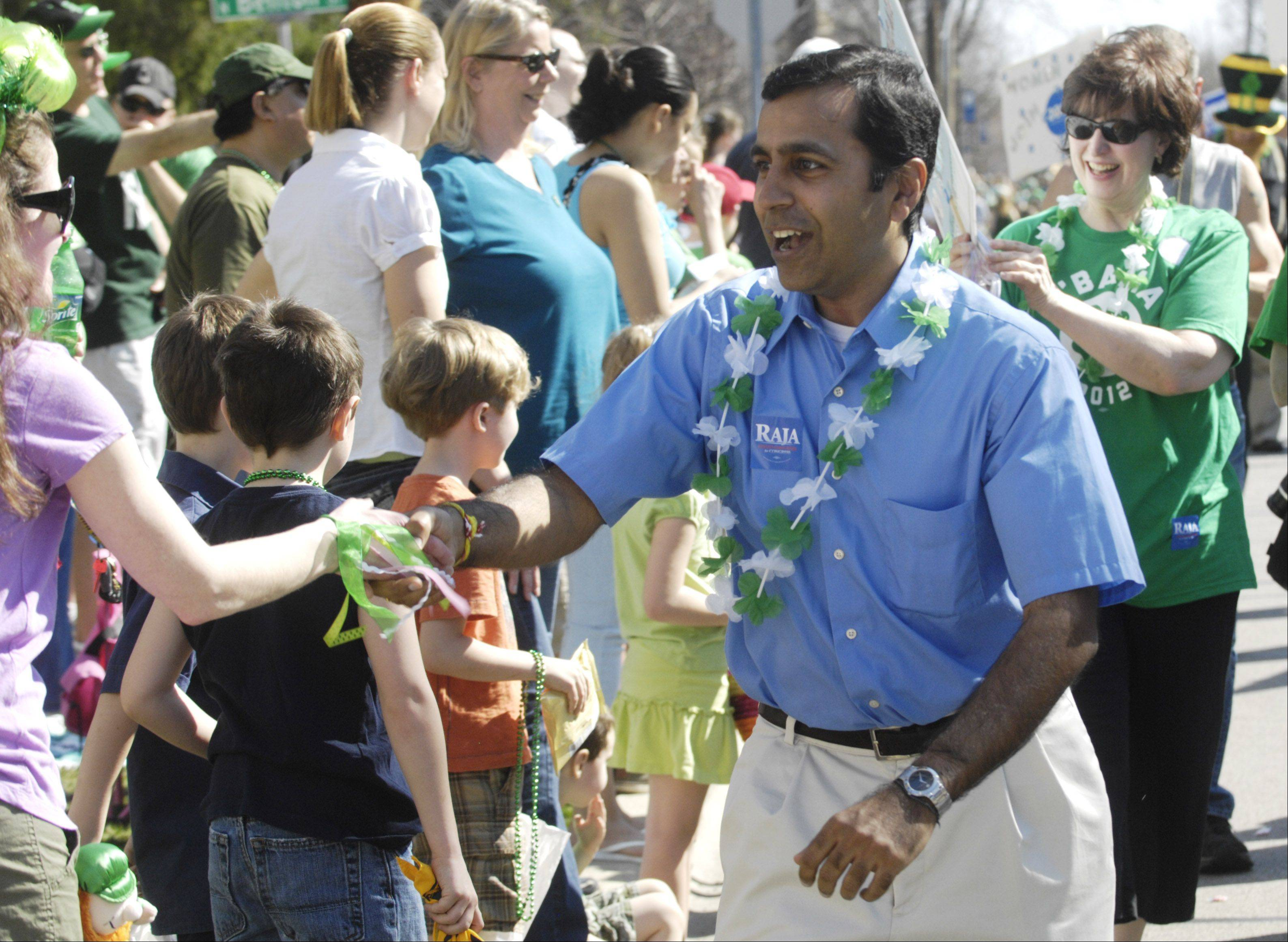 Decked out for the day in a shamrock lei, Raja Krishnamoorthi, Democratic candidate for the 8th Congressional District, greets crowds lining Wood Street on Saturday during the Palatine St. Patrick's Day Parade.