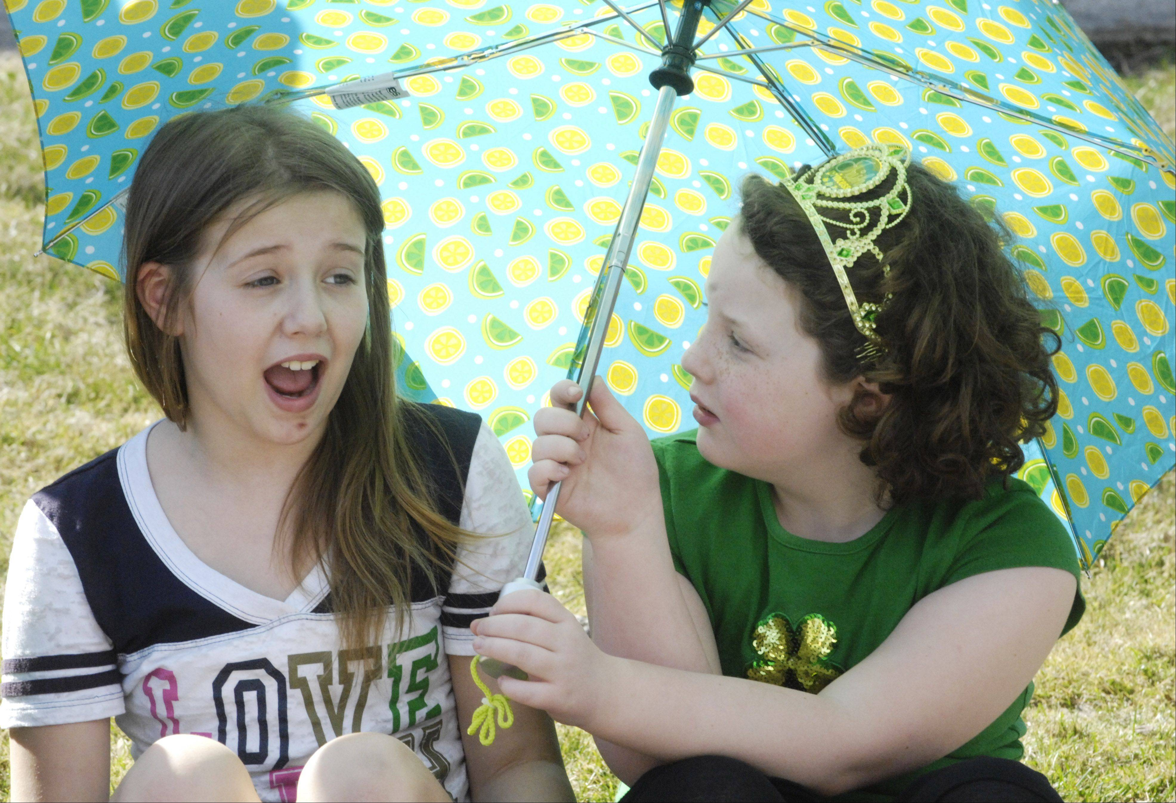 Rachel Jordan, 10, left, and Maddie Dolezal, 8, both of Cary, shade themselves from the warmth of the sun while awaiting the start of the Palatine St. Patrick's Day Parade Saturday.