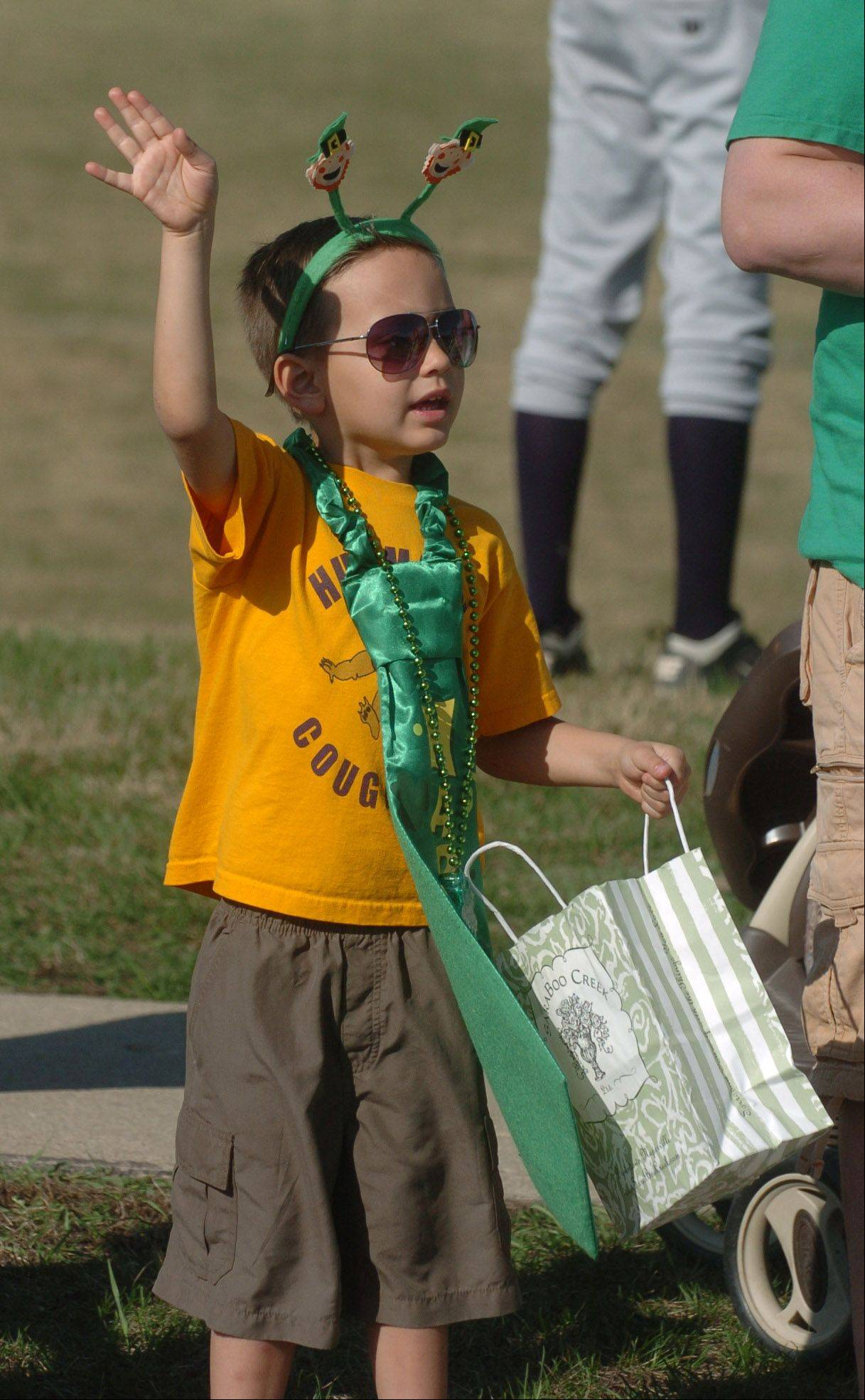 Colin Brown,5, of Naperville waves to the folks in the parade in hope of getting candy during the St. Patricks day parade in Naperville Saturday. Well over 3,000 people took part in this event that was complemented by beautiful weather.