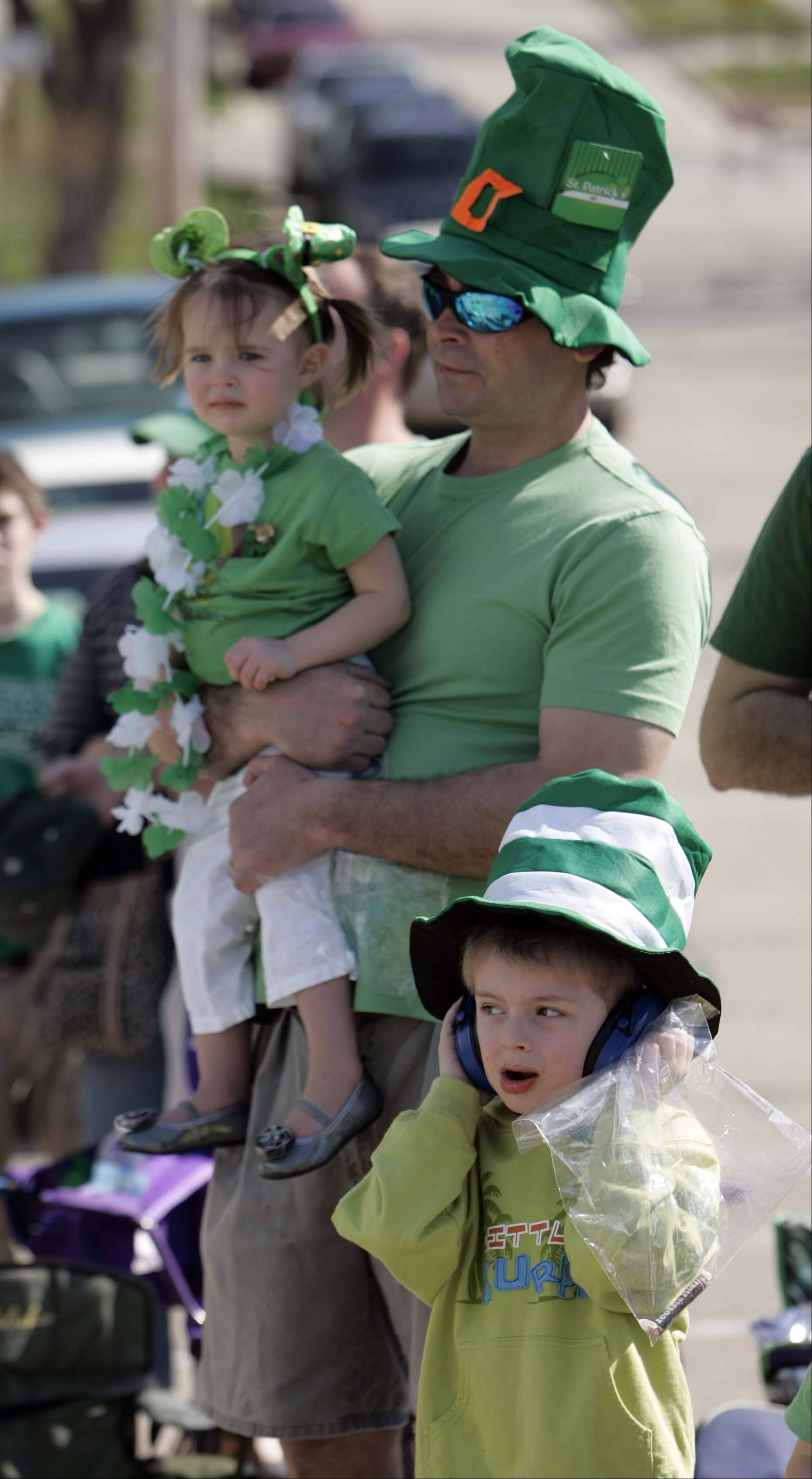 John Smith of Palatine holds his two-year-old daughter Grace while his son John Jr., 5, covers his ears as the Thom McNamee Memorial St. Patrick's Day Parade makes it way thru East Dundee March 17, 2012.