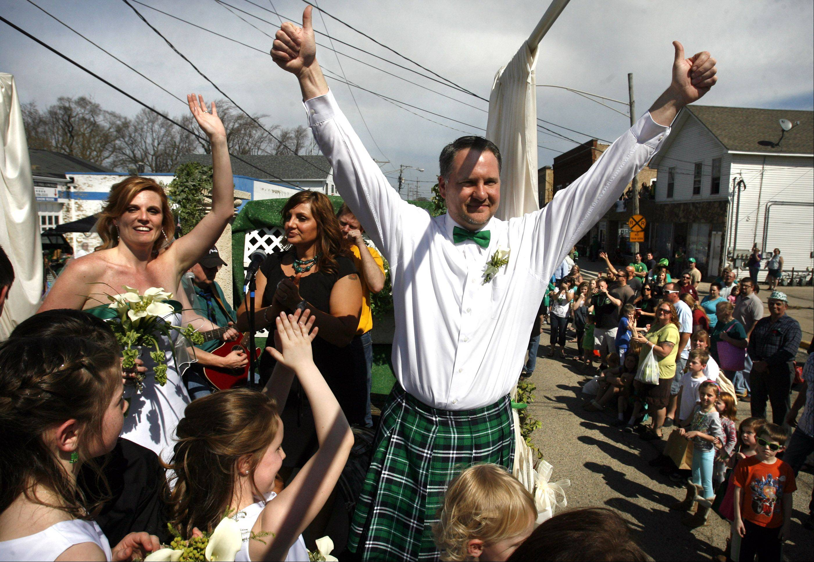 Tara Teschky and Paul Quinn of Libertyville wave to crowd after getting married on a float during the Lake Villa St. Patrick's Day parade on Saturday, March 17th.