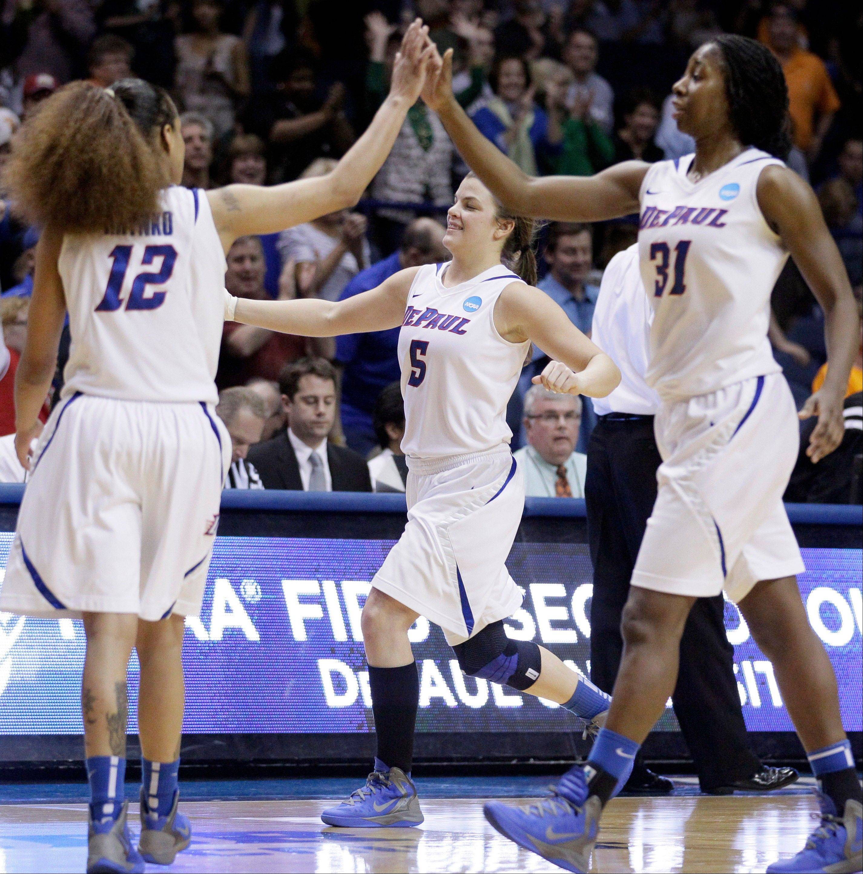 DePaul guard Anna Martin (5), guard Brittany Hrynko (12) and forward Jasmine Penny (31) celebrate after they defeated BYU 59-55 during an NCAA tournament first-round women's game.