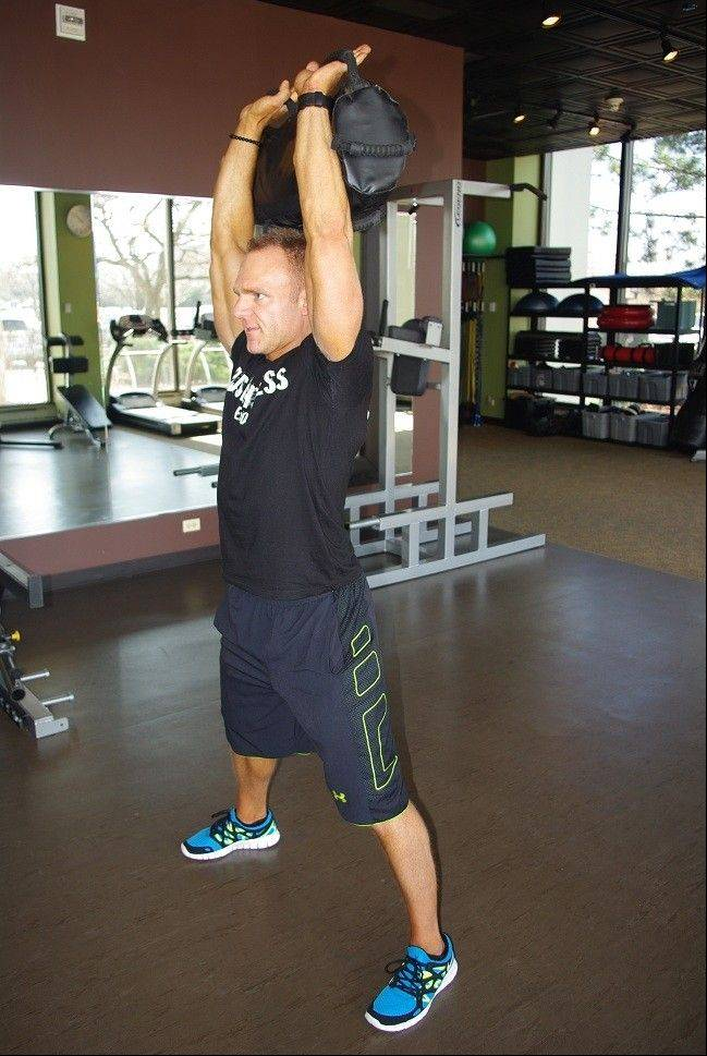 Third step in the sandbag burpee to press. Pull the sandbag upward as you flip it to shoulder height and then press it overhead. Repeat in a fluid motion.