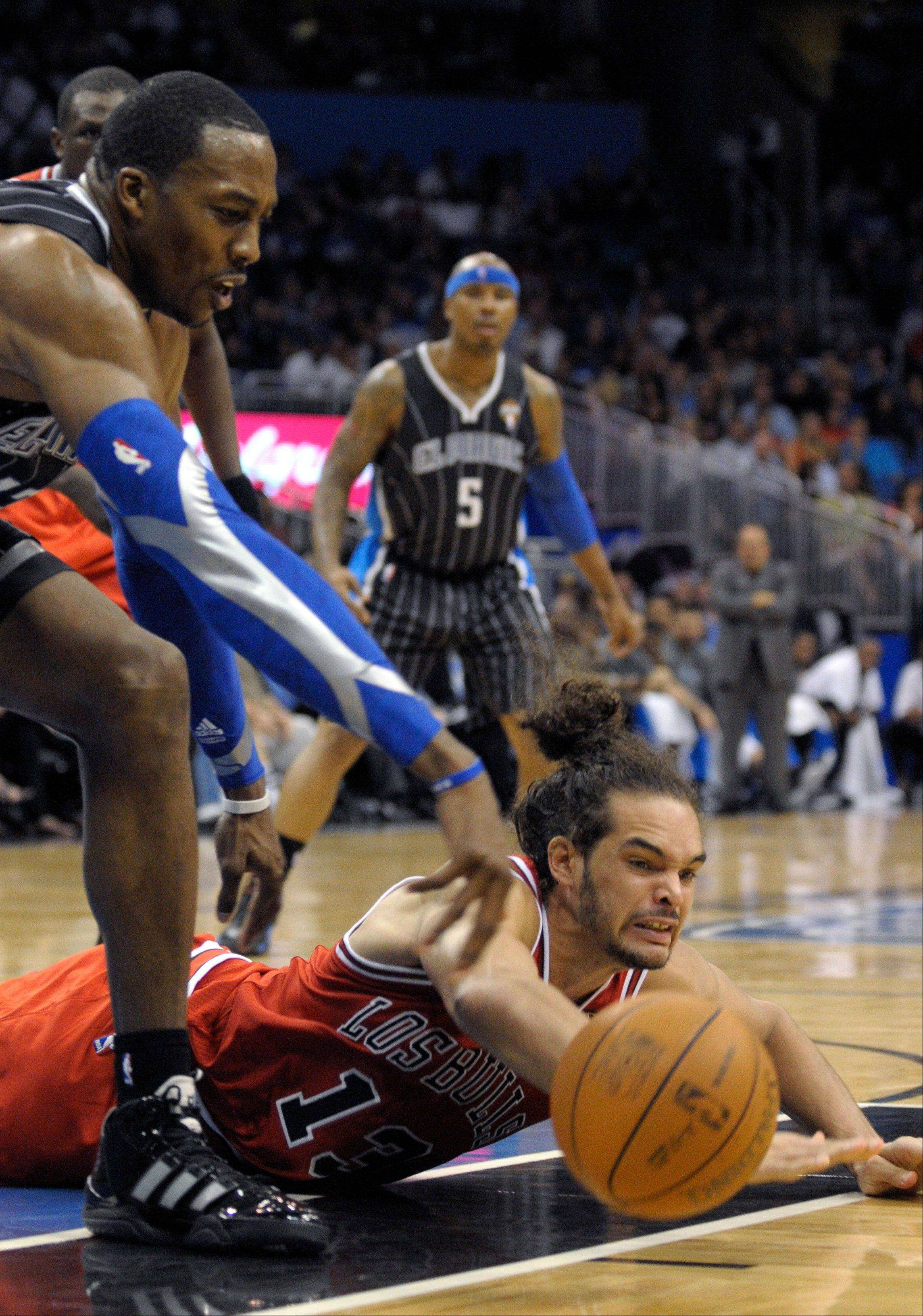 Orlando Magic center Dwight Howard, left, and Chicago Bulls center Joakim Noah battle for the loose ball as Quentin Richardson watches during the second half Monday in Orlando.