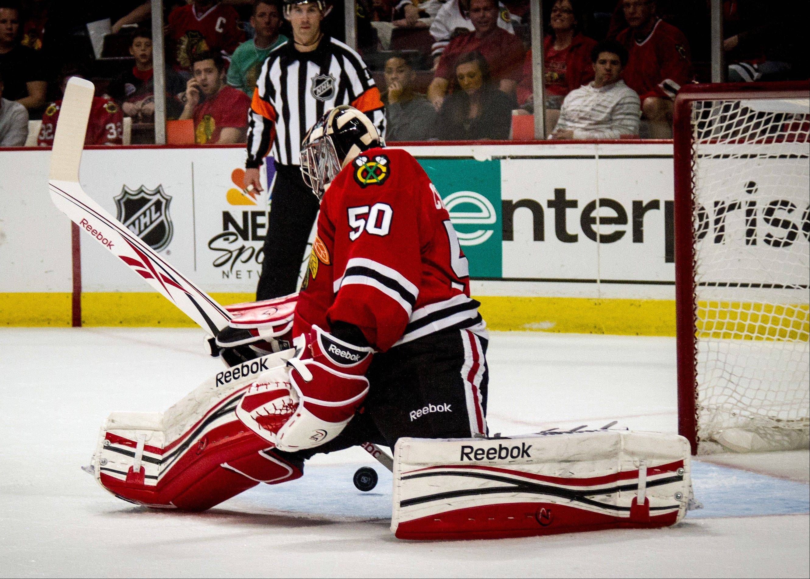 Chicago Blackhawks goalie Corey Crawford finds puck behind him and makes the save during the first period against the Washington Capitals in an NHL hockey game in Chicago on Sunday, March 18, 2012.