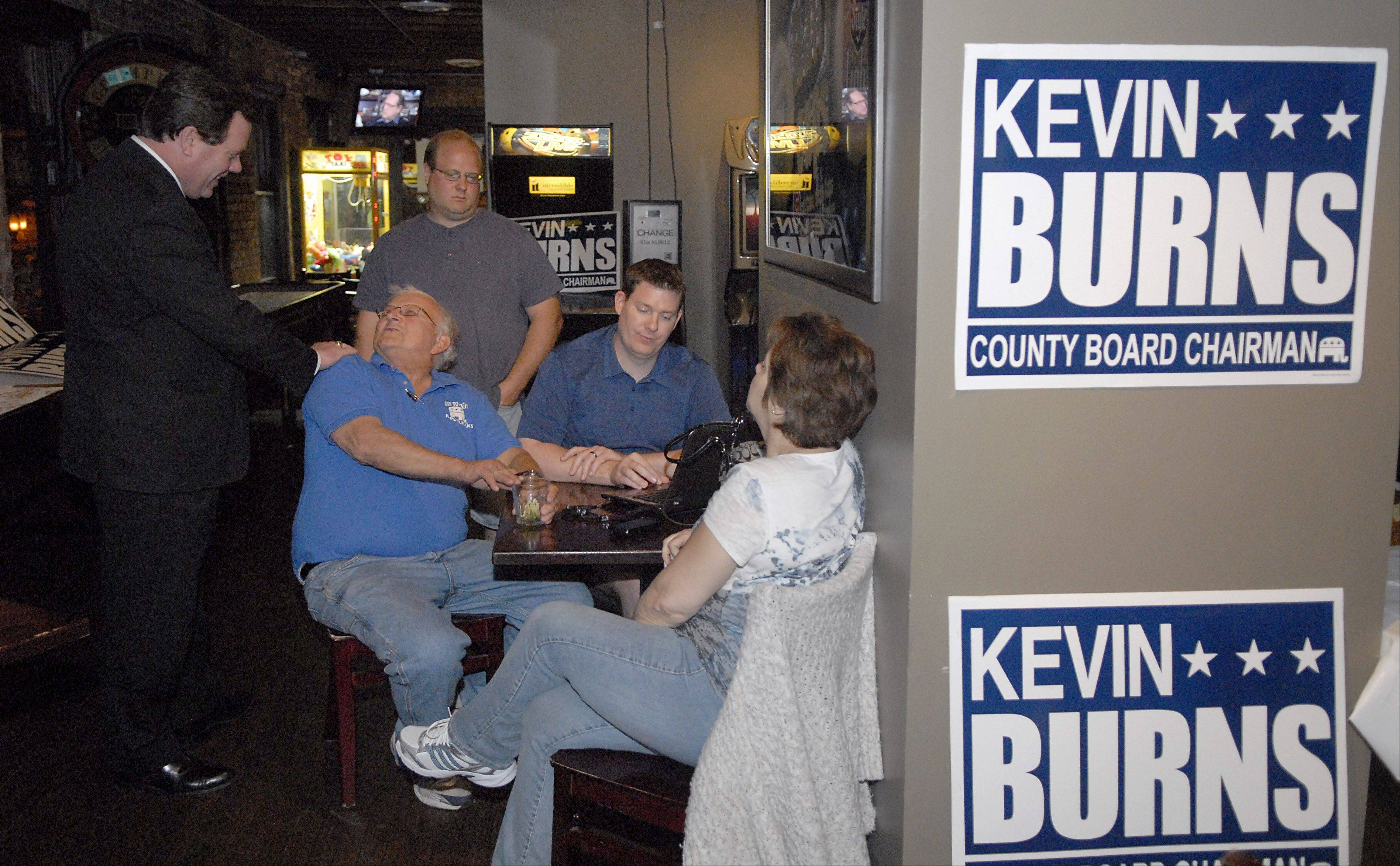 While campaign staffer Chris Brown checks results, Kane County Board Chairman Republican candidate Kevin Burns jokes with Kane County Board member Mike Kenyon of South Elgin at his election night party in Geneva on Tuesday. Jerry Cass of Geneva and Batavia Township Chairman Ellen Notke also wait for results to come in.