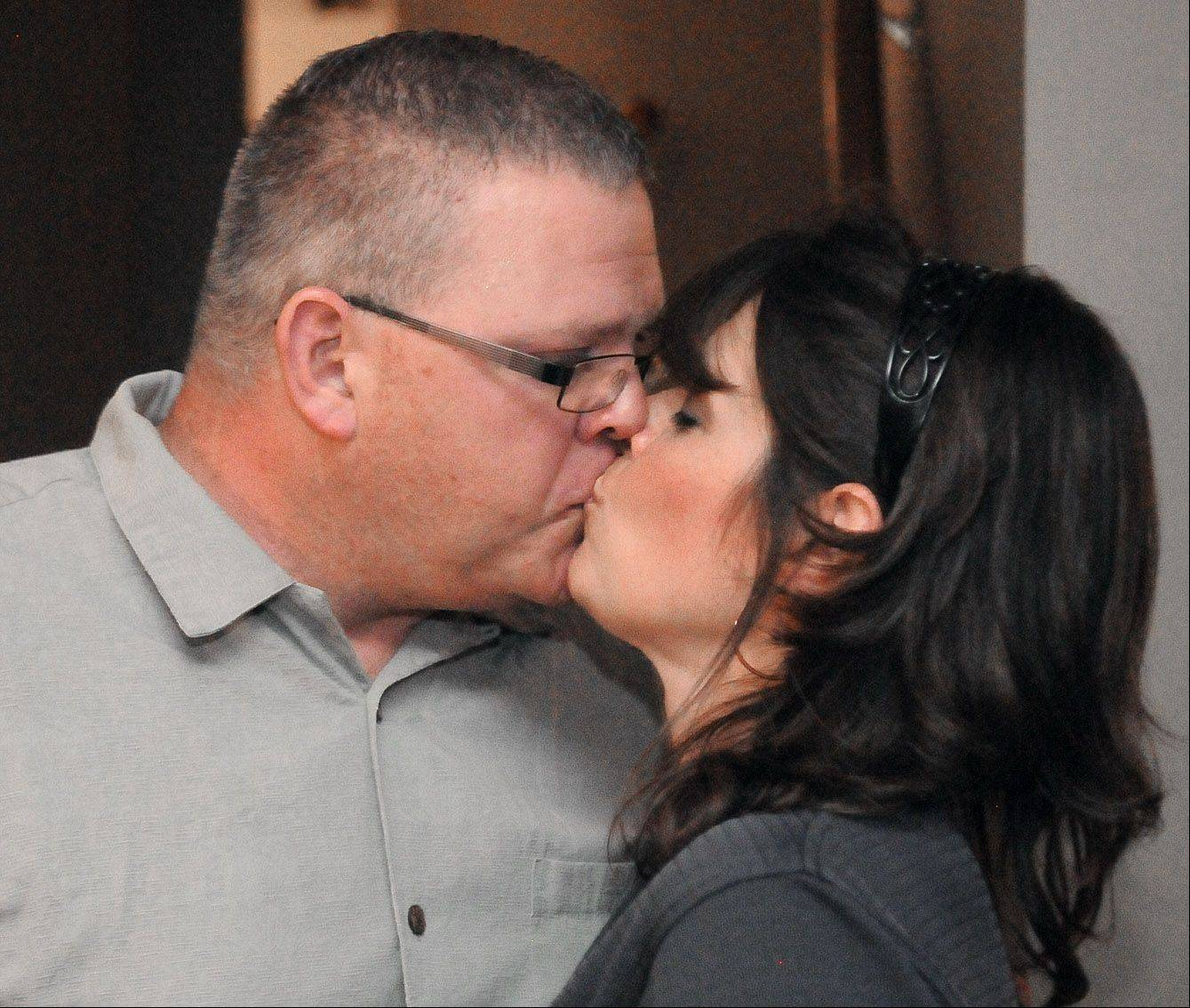Laura Stoecker/lstoecker@dailyherald.comRepublican Kane County coroner candidate Rob Russell gives his wife, Susan, a kiss during his election night party at their South Elgin home on Tuesday. Russell had just announced to his family, friends, children and other supporters he was in the lead and was thankful to all of them for helping him during the election.