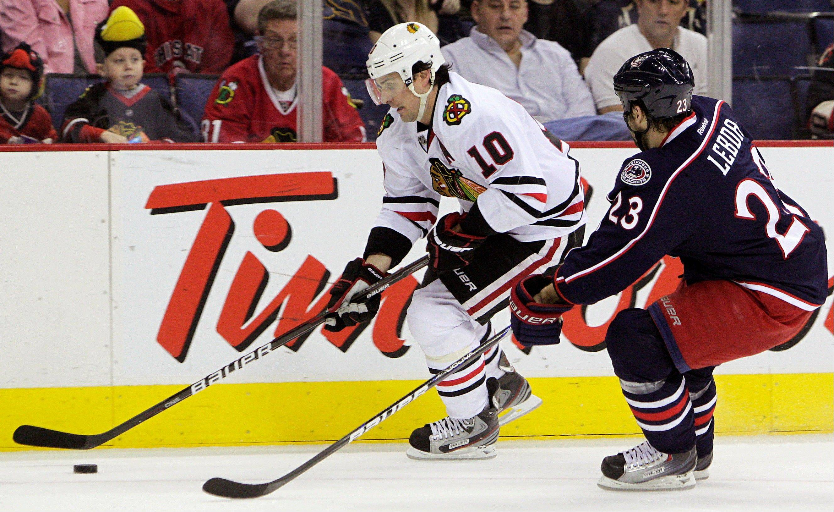 Blackhawks forward Patrick Sharp carries the puck up ice as Columbus Blue Jackets' Brett Lebda defends Tuesday during the first period.