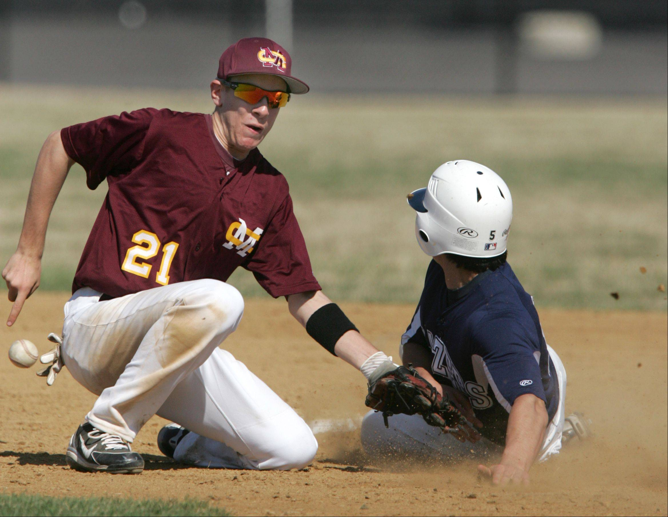 Addison Trail runner Carlos Dorado steals second base and advances to third as Montini's Eddie Bava, 21, tries to come up with the ball.