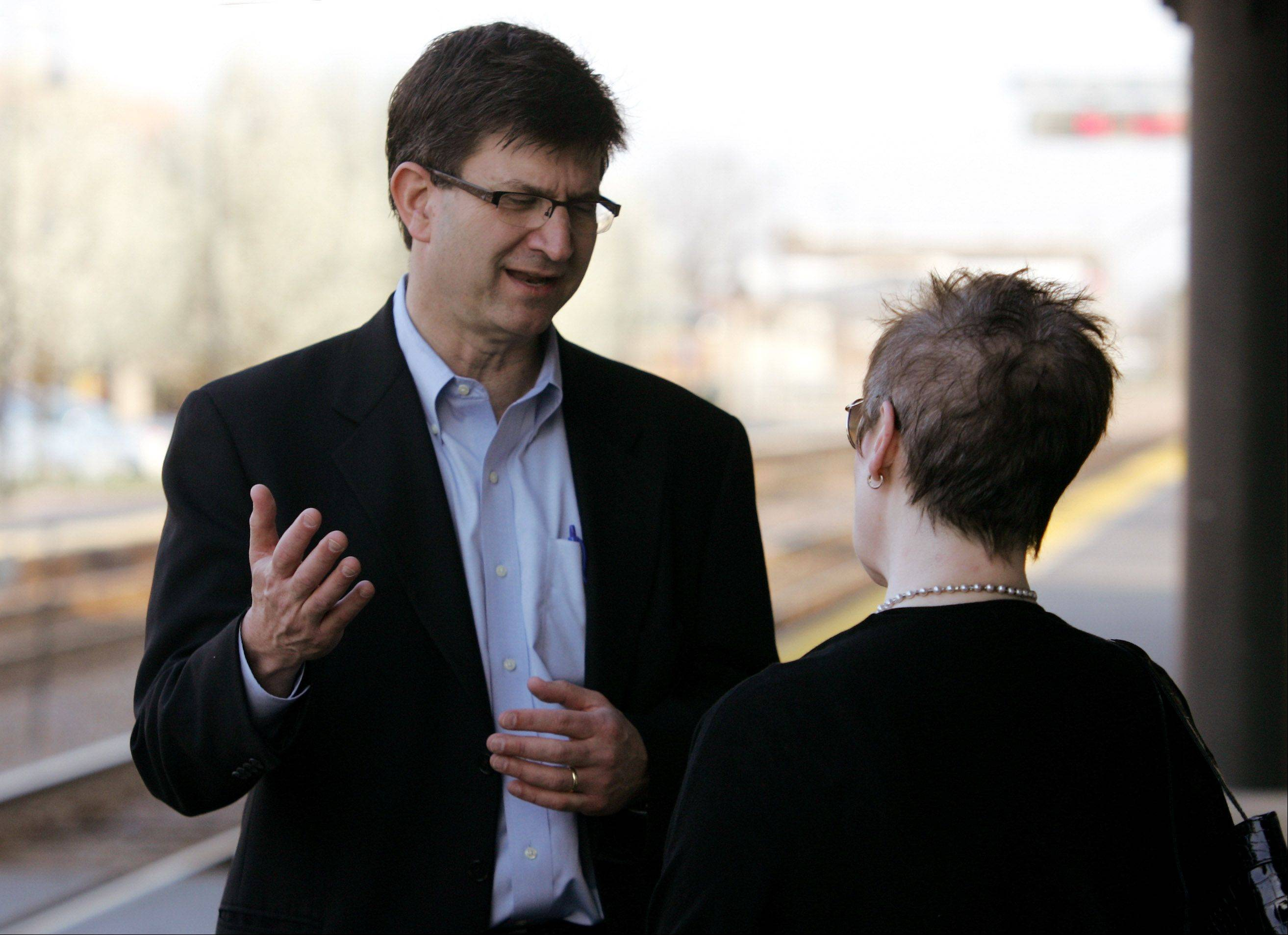 Tenth Congressional District candidate Brad Schneider talks to Highland Park resident Leslie Cole on Wednesday morning at that city's train station.