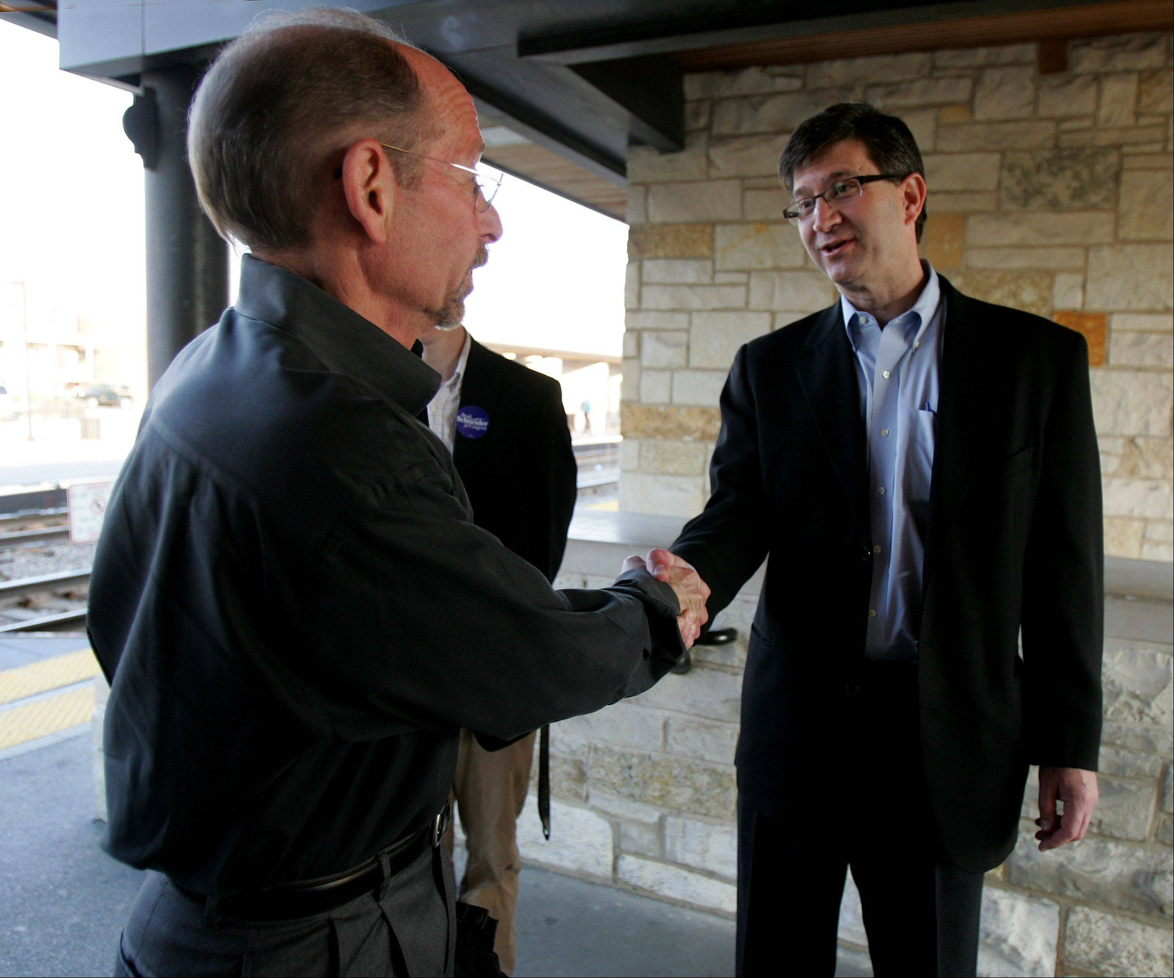 Tenth Congressional District candidate Brad Schneider, right, shakes hands with commuter Stephen Marcus. Schneider, of Deerfield, greeted commuters at the Highland Park train station Wednesday morning, a day after his primary win.