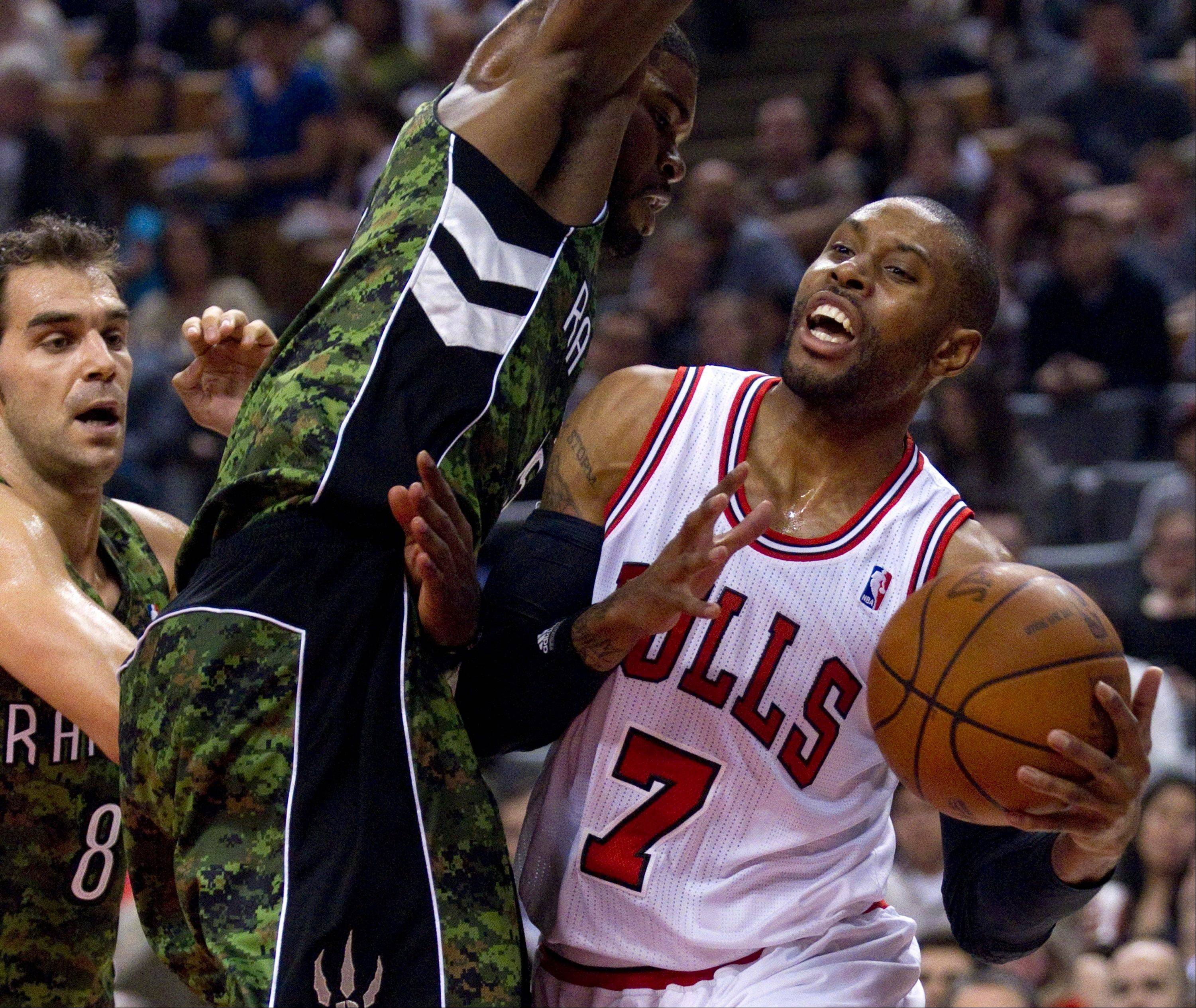 Bulls guard C.J. Watson drives to the hoop past the Toronto Raptors' Amir Johnosn, center, and Jose Calderon Wednesday.
