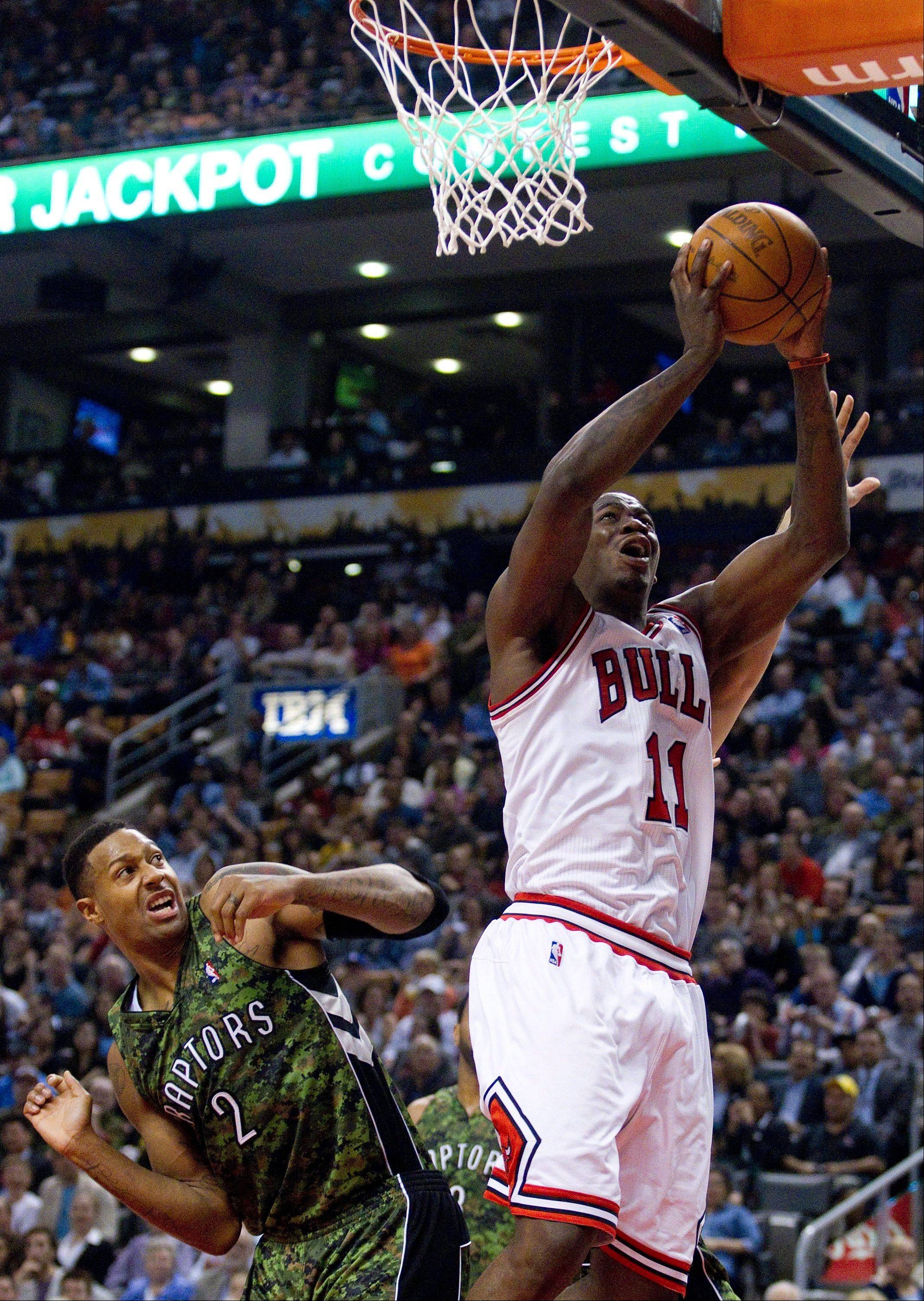 Bulls guard Ronnie Brewer jumps to the net past the Toronto Raptors' James Johnson Wednesday during the first half.