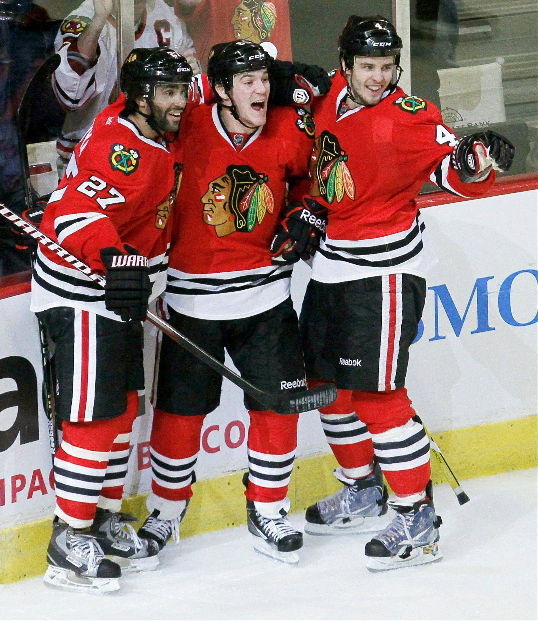 The Blackhawks' Andrew Shaw, center, celebrates his game-winning overtime goal Wednesday with Johnny Oduya (27) and Niklas Hjalmarsson.