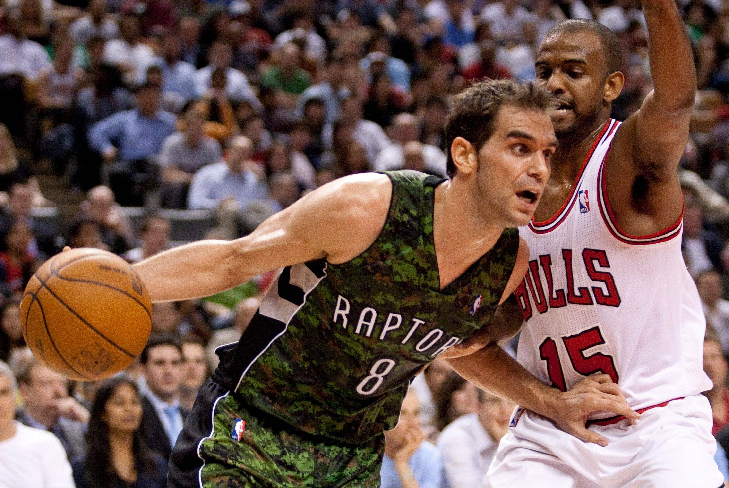 The Toronto Raptors' Jose Calderon, left, drives to the net past Bulls guard John Lucas III Wednesday during the second half.