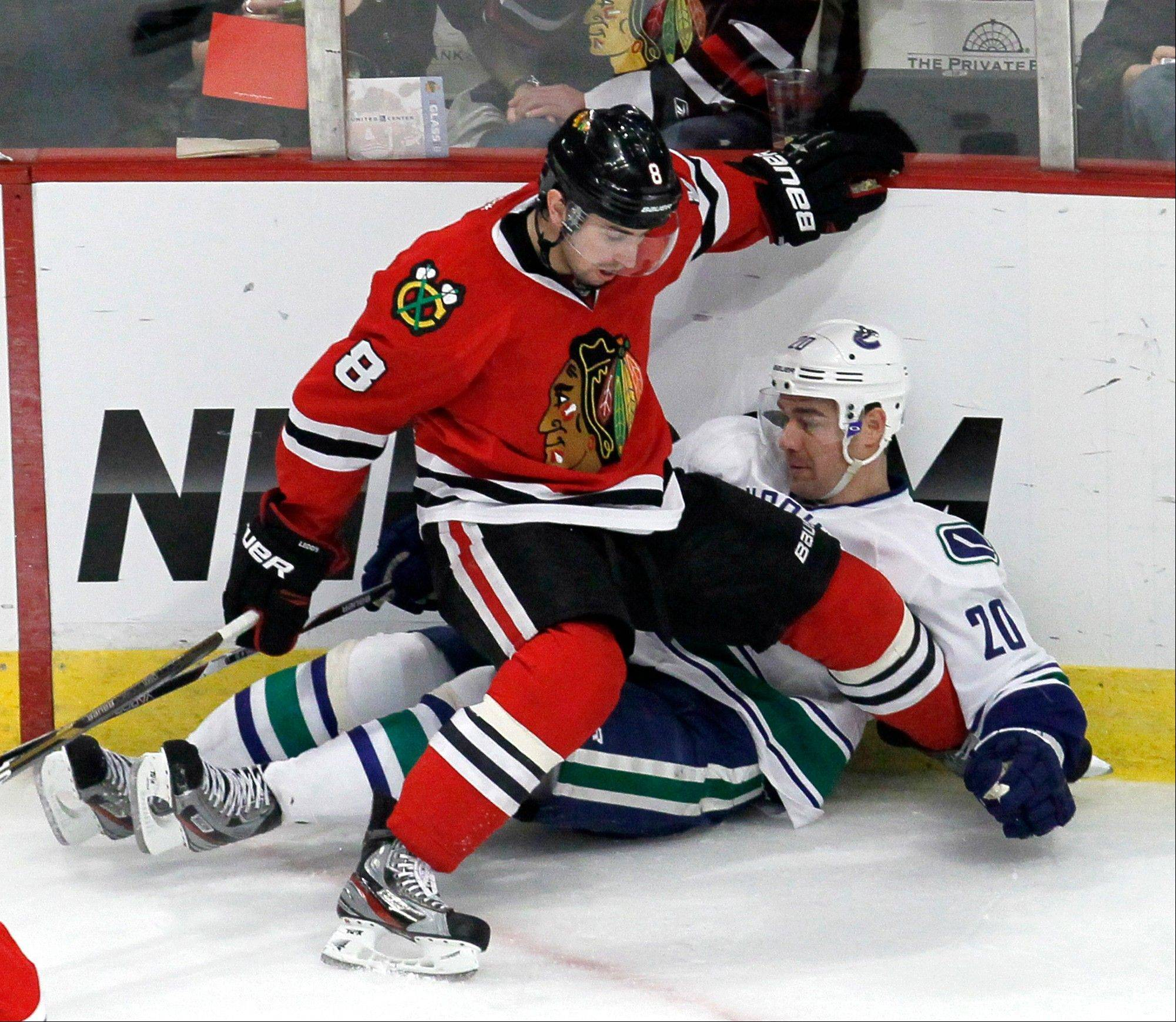 Blackhawks defenseman Nick Leddy checks Vancouver Canucks left wing Chris Higgins along the boards Wednesday during the third period.
