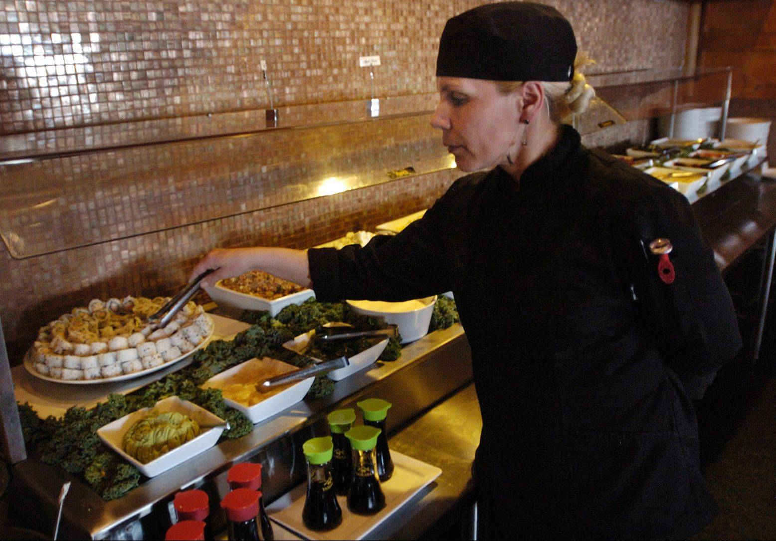 Chef Angelica Russomano sets up the salad bar that includes fresh sushi at Sake & Samba Brazilian Churrascaria in Vernon Hills.