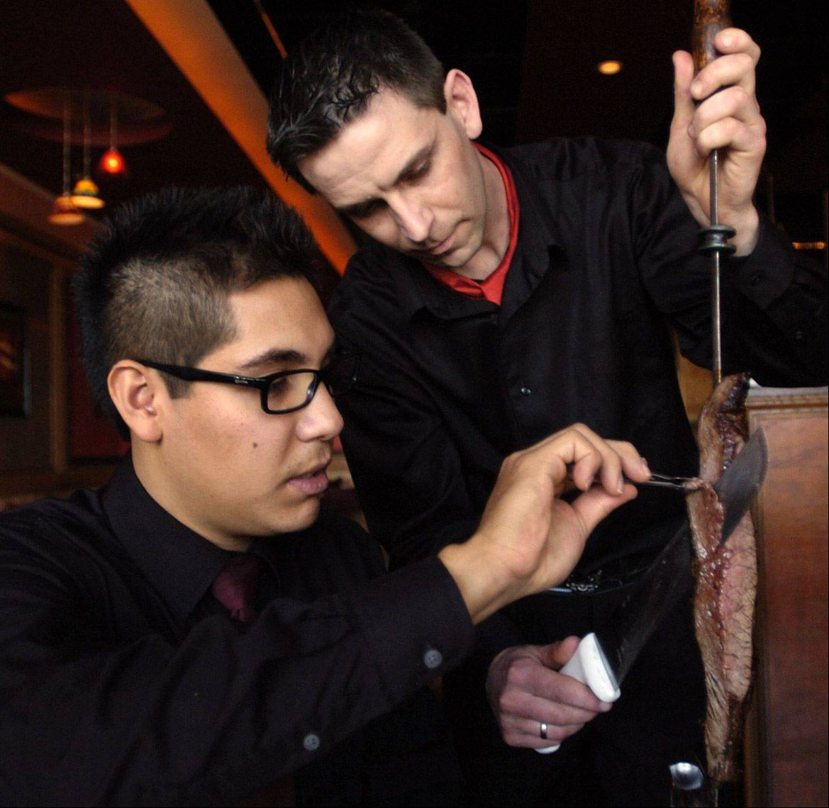 Floor manager Edgar Hernandez slices some flank steak from gaucho Paulo Derkascz at Sake & Samba in Vernon Hills.