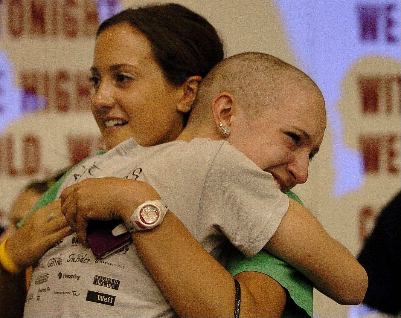 Erin Falsey gets hugged by her sister Collette, left, who had cancer as a child. Erin raised $3300. in her sisters name at the St. Baldrick's head shaving event at Schaumburg High School.