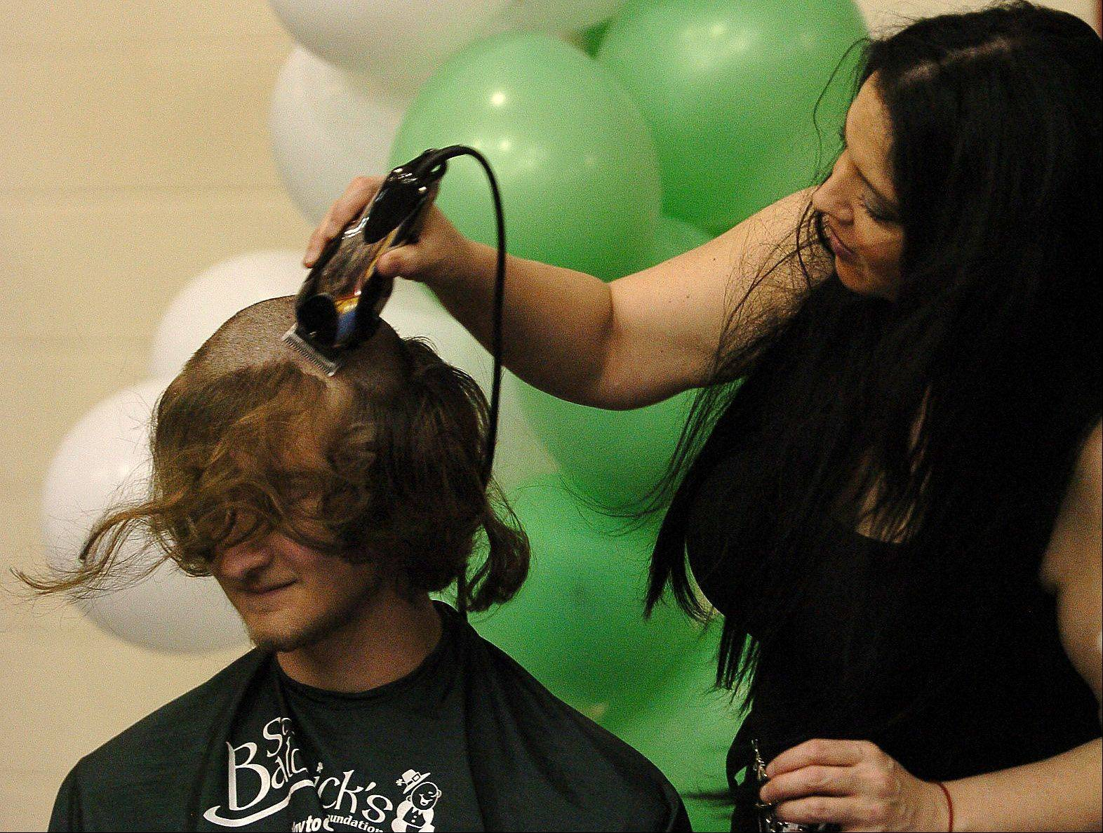 Justin Pacocha gets his head shaved by Laura Quintero of Sport Clips during the St. Baldrick's head shaving event at Schaumburg High School.