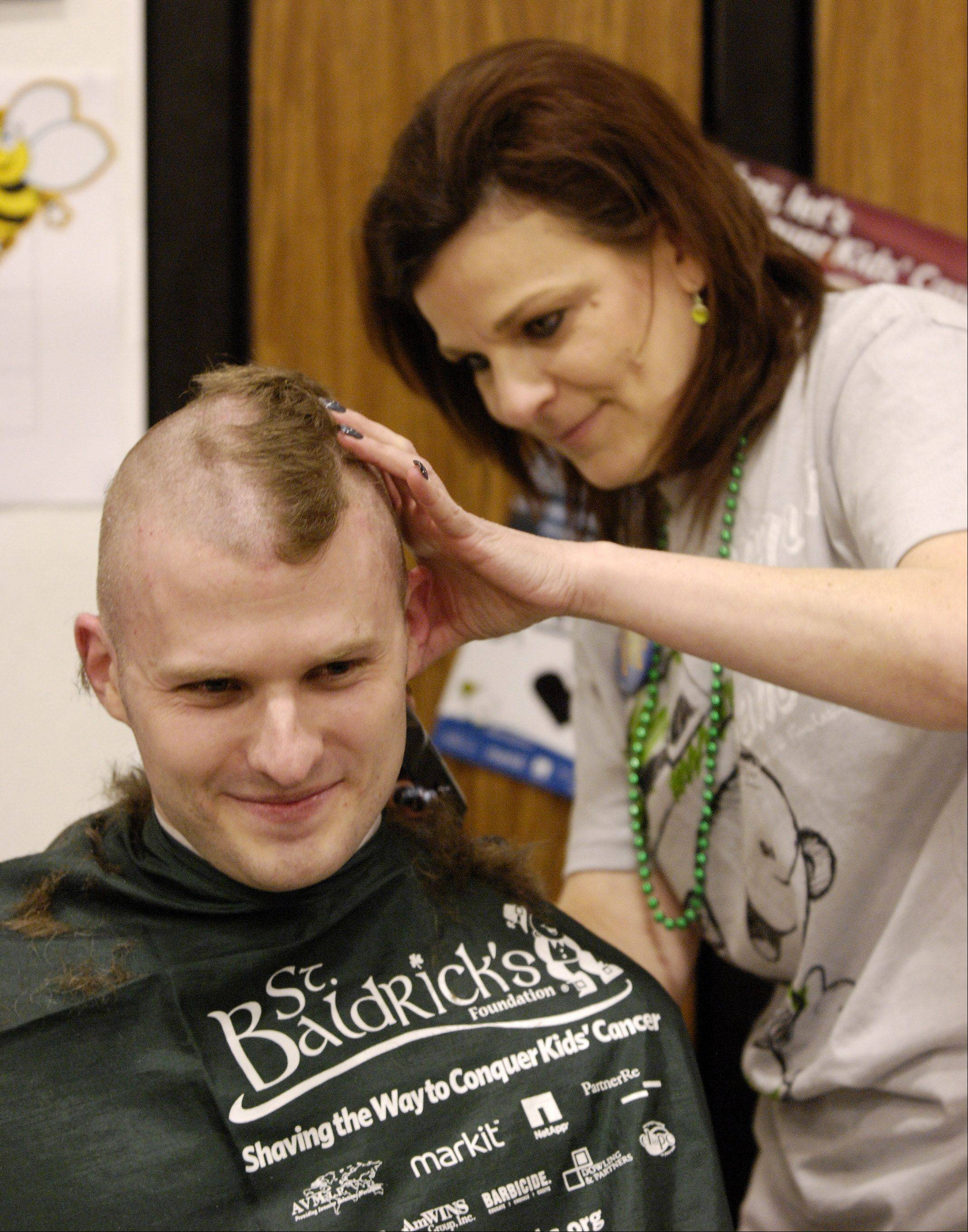 Joshua Kairis of South Elgin and the computer teacher at Evergreen School, has his head shaved by Anna Sarnelli during a St. Baldrick's fundraiser at Evergreen School in Carol Stream, for second grader Jack O'Donoghue who has Burkitt's lymphoma, a non Hodgkin's cancer of the lymphatic system, Sunday.