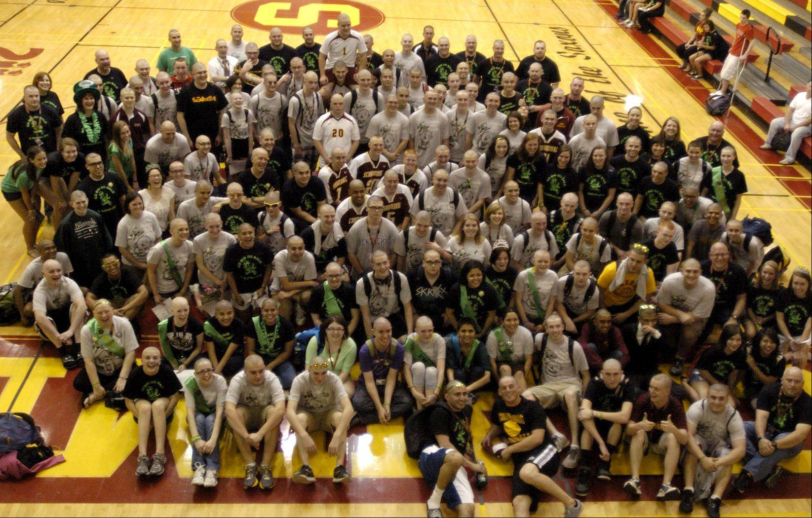Everyone who got their head shaved pose for a shot on the gym floor after the St. Baldrick's head shaving event at Schaumburg High School.