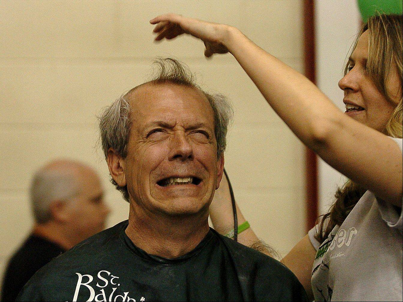 Band Director Kevin Miller gets his head shaved by Josette Martiny of Sport Clips during the St. Baldrick's head shaving event at Schaumburg High School.