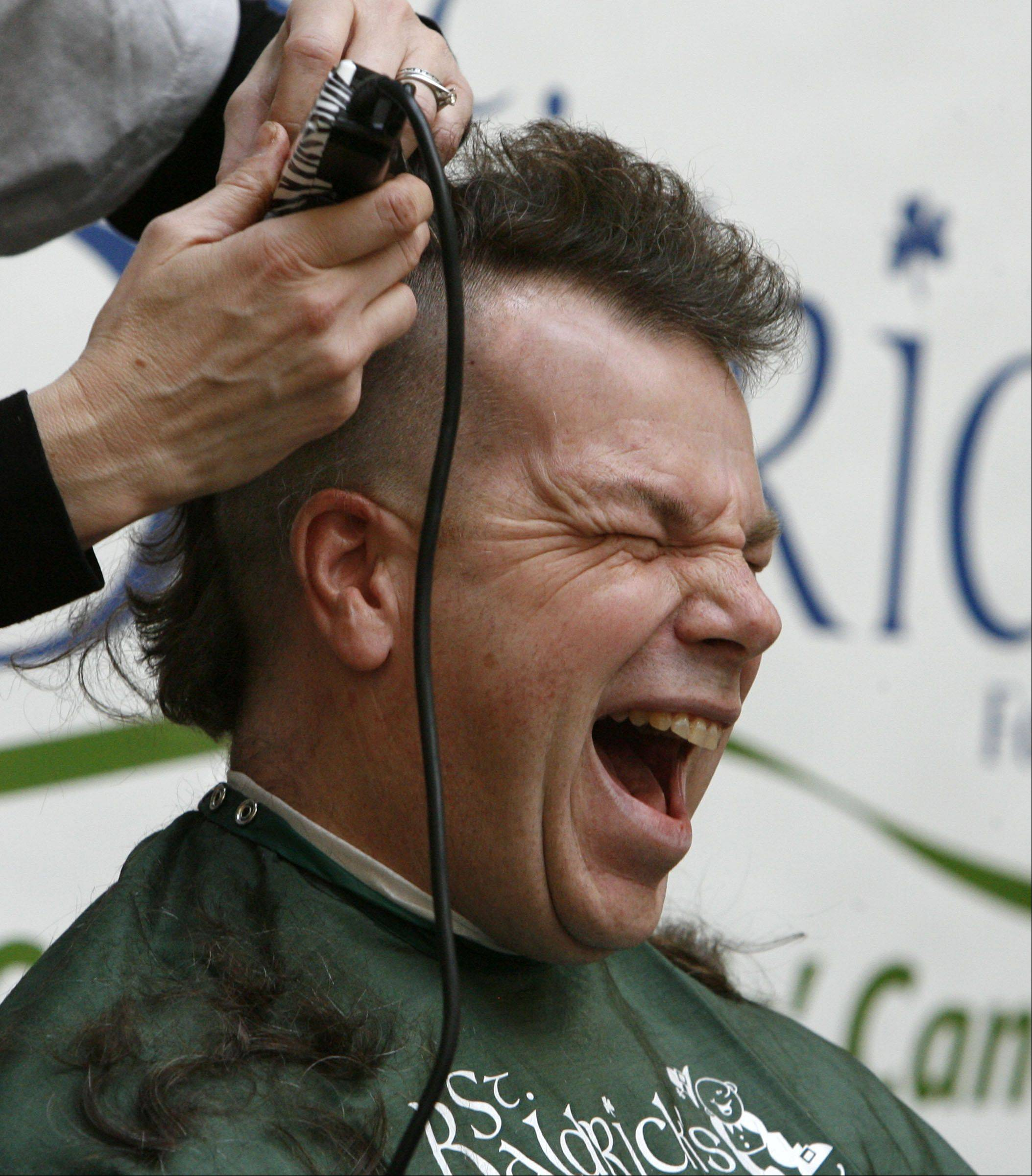 Vernon Hills Police officer Ward Feger reacts to having his head shaved by Martie Gross, with Natural Beauty Salon in Wisconsin, during the Vernon Hills St. Baldrick�s event, to raise money to fight childhood cancer, held at Westfield Hawthorn Mall in Vernon Hills on Saturday, March 10th.