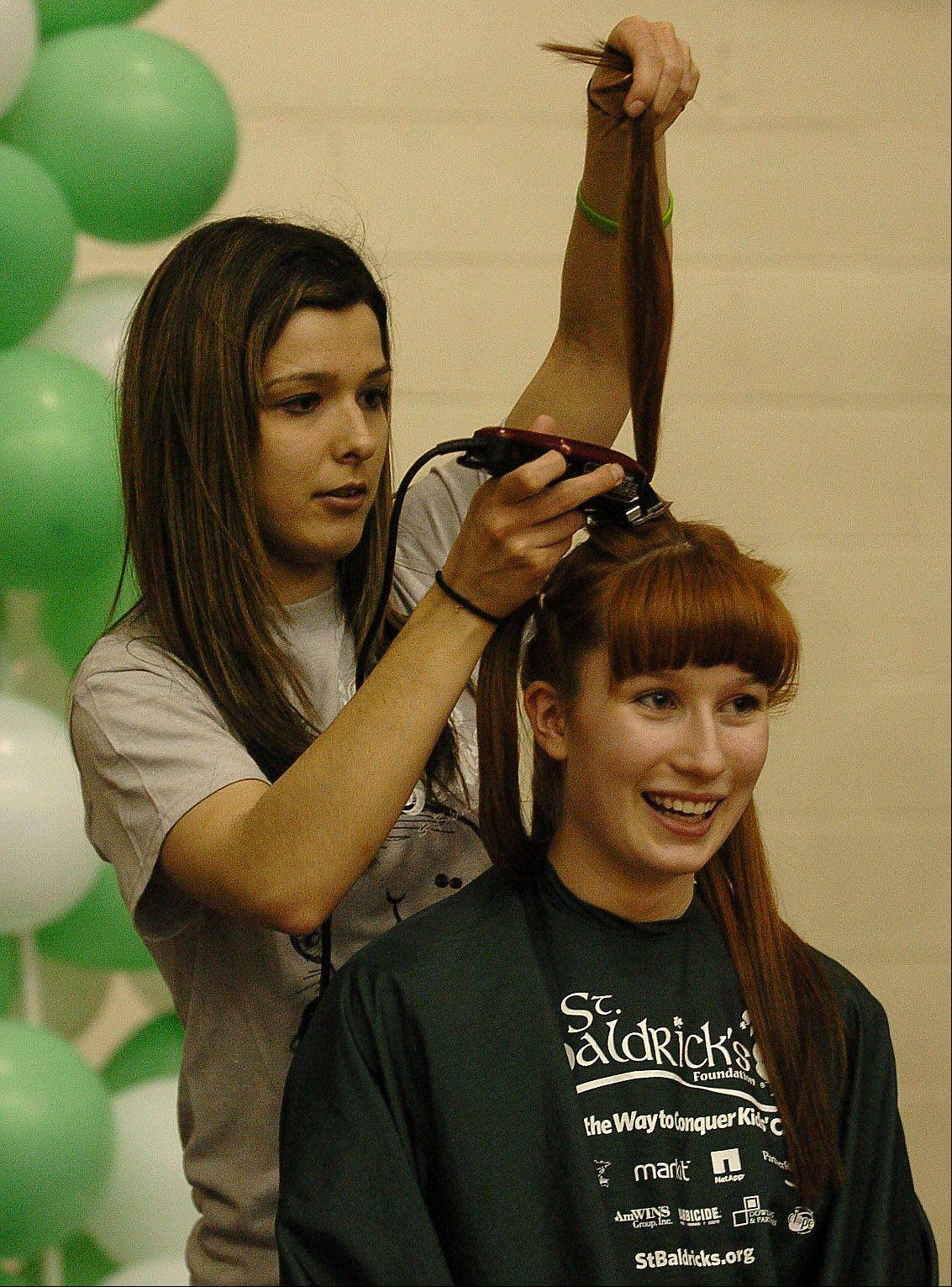 Olivia Zubko who raised $1320., gets her hair cut by Shari Rensberger of SportClips during the St. Baldrick's head shaving event at Schaumburg High School.