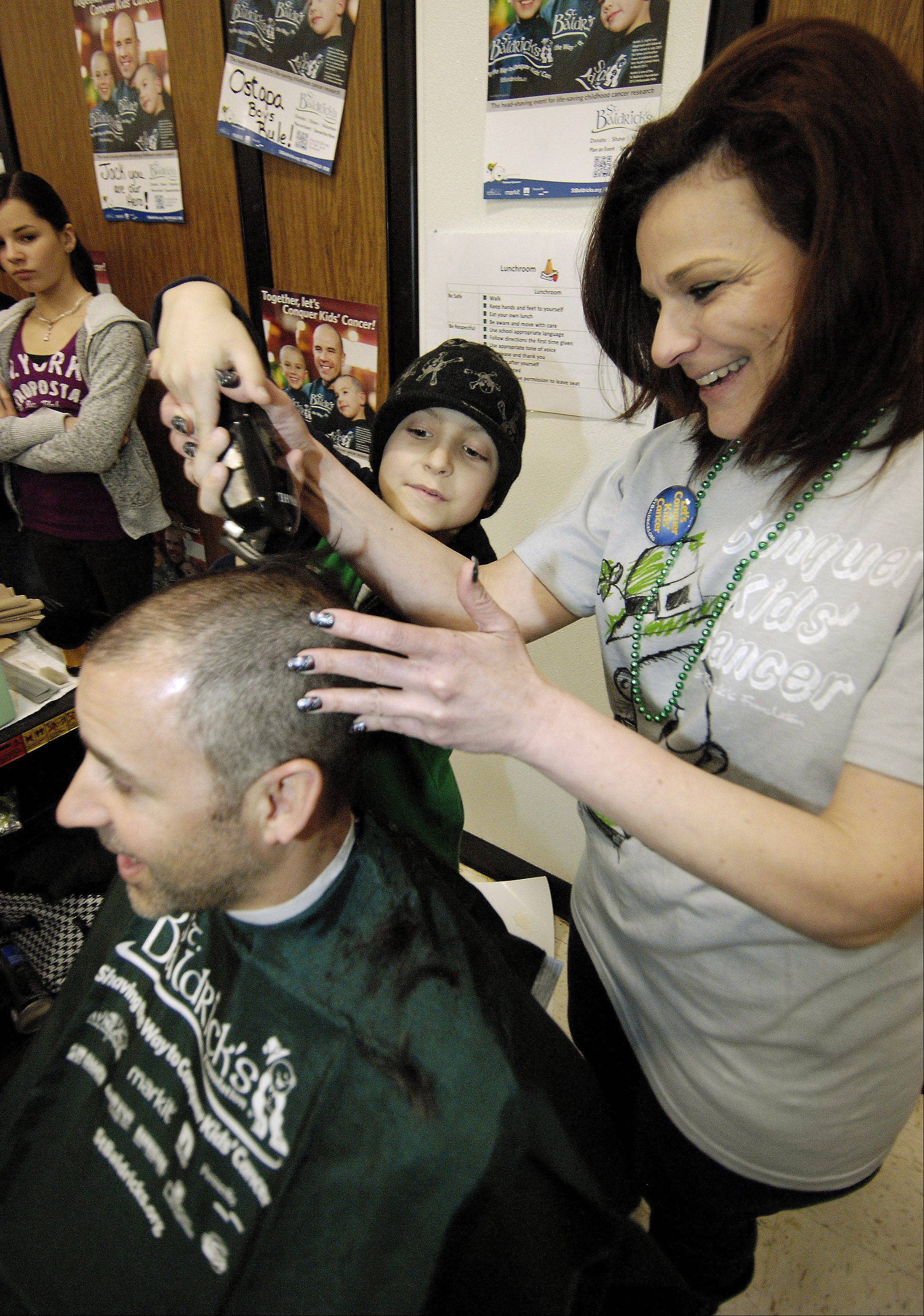 Jack O'Donoghue helps Anna Sarnelli shave the head of his godfather Steve Bisbikis, during a St. Baldrick's fundraiser at Evergreen School in Carol Stream for him. Jack has Lymphoma, a non Hodgkin's cancer of the lymphatic system, Sunday.