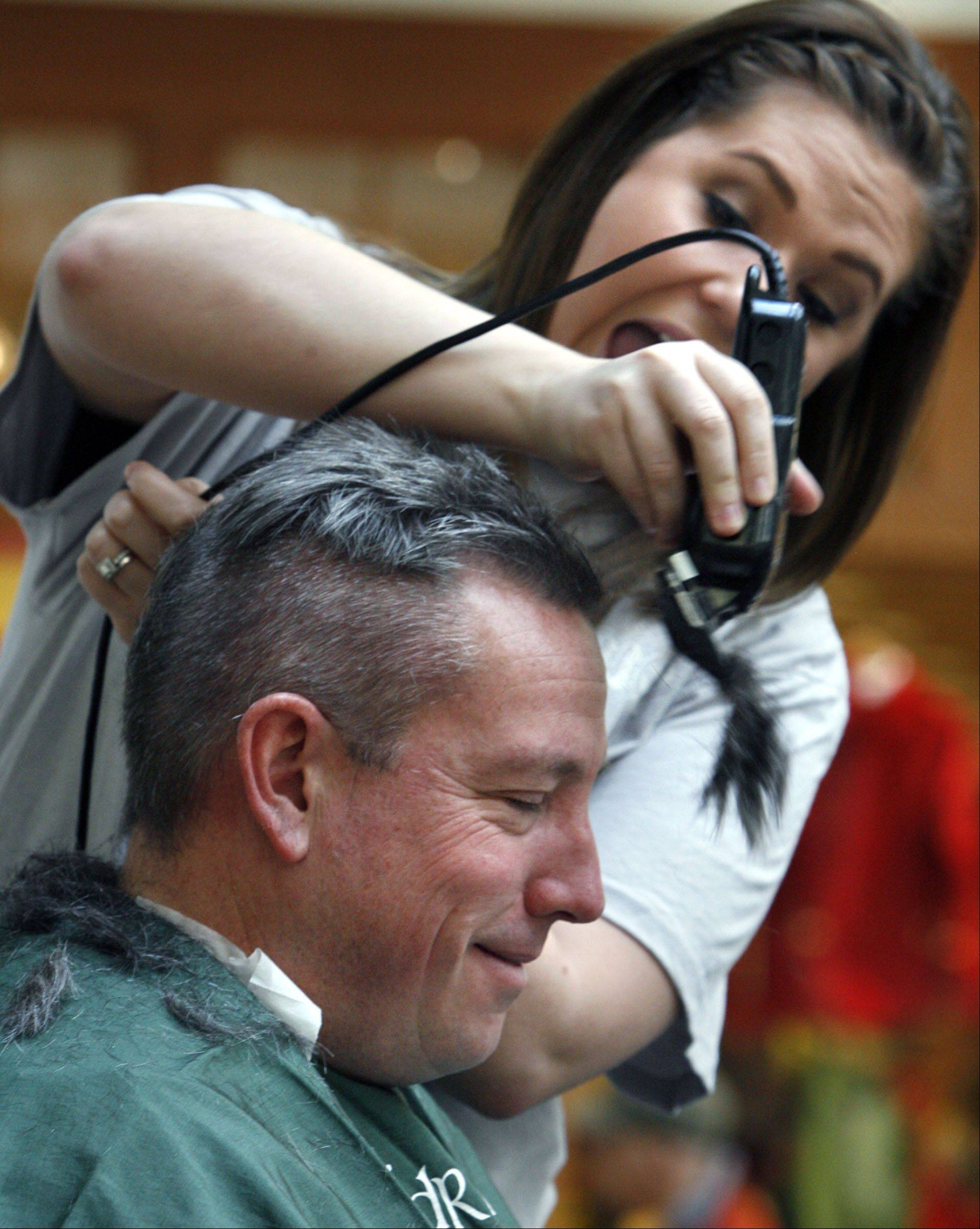 The hair flies off as Vernon Hills Police SGT Todd Williams has his head shaved by Angela Schramm, with Mario Tricoci Salon in Libertyville, during the Vernon Hills St. Baldrick�s event, to raise money to fight childhood cancer, held at Westfield Hawthorn Mall in Vernon Hills on Saturday, March 10th..