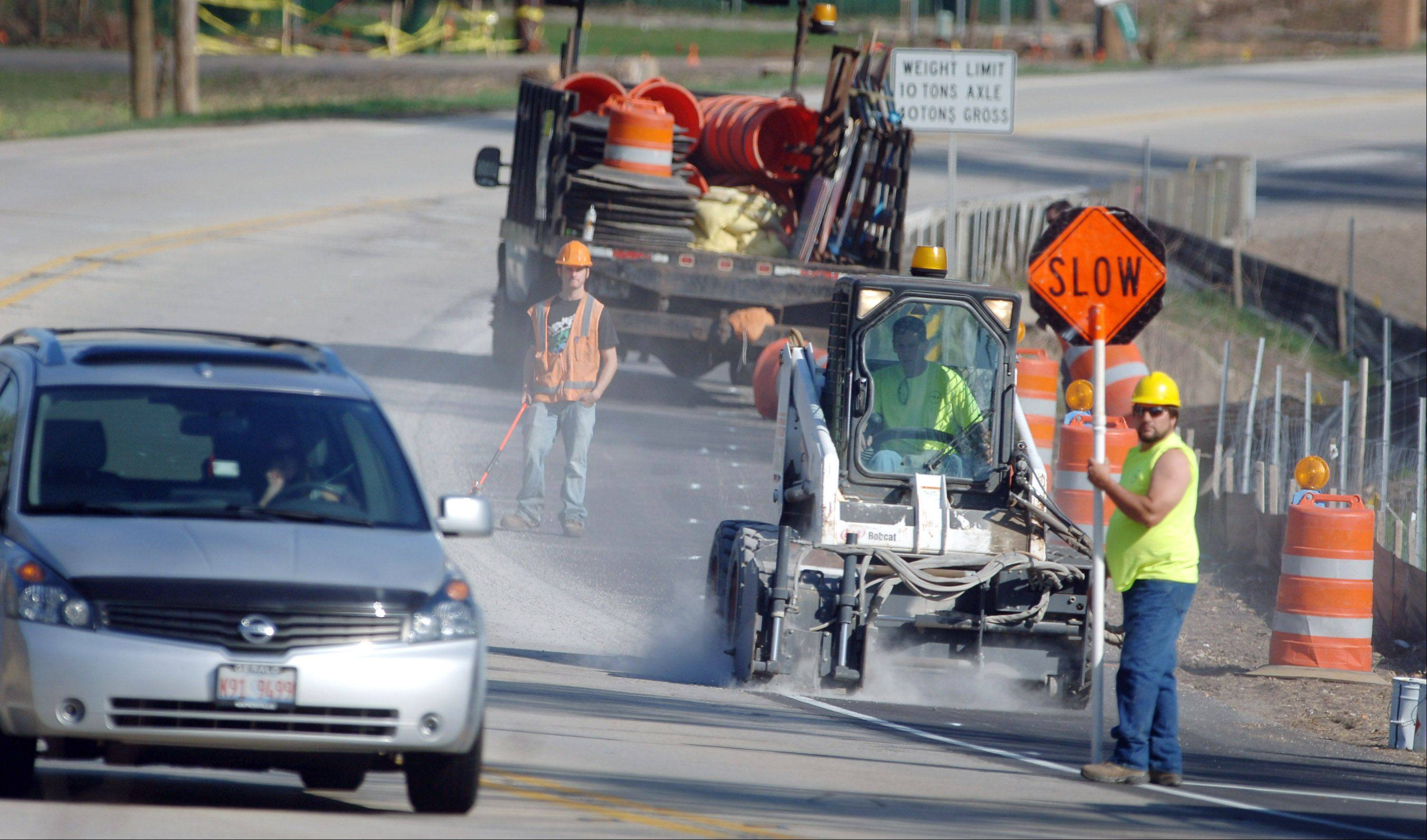 Crews remove painted lane markers Thursday morning to make way for new traffic patterns along Milwaukee Avenue north of Libertyville.
