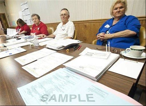 Election judges in North Pekin, in Tazewell County await voters after trimming one-eighth of an inch off of ballots in Pekin's 25th precinct. Tazewell County was one of about 25 counties in the state reporting problems with similar ballots.