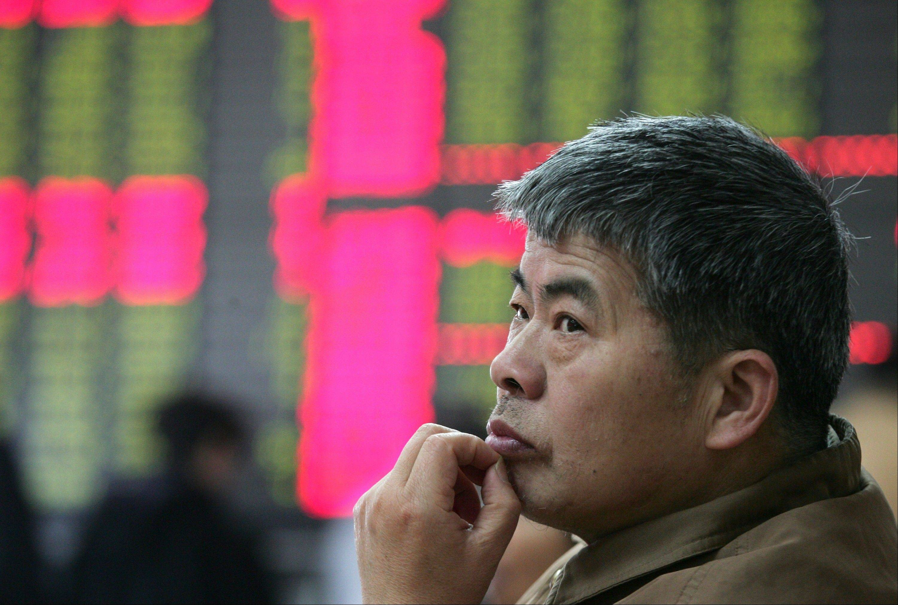 An investor looks at the stock price monitor at a private securities company in Shanghai, China, Friday.