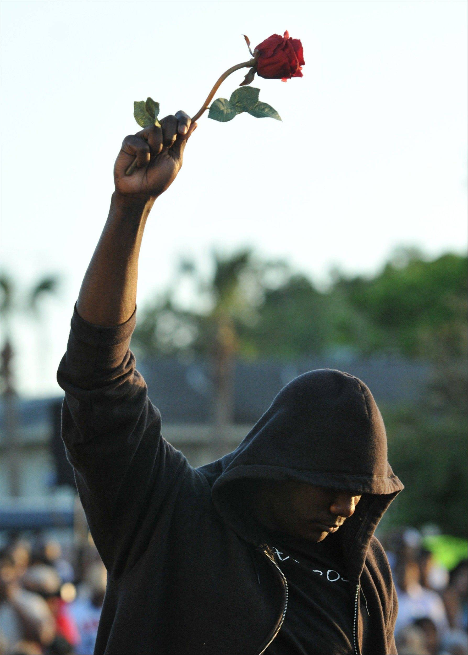 Wearing a hoodie and holding a rose, James Gilchrist of Orlando, Fla., attends a rally for Trayvon Martin, the teen shot by George Michael Zimmerman while on Neighborhood Watch patrol, Thursday, March 22, 2012 in Sanford, Fla.