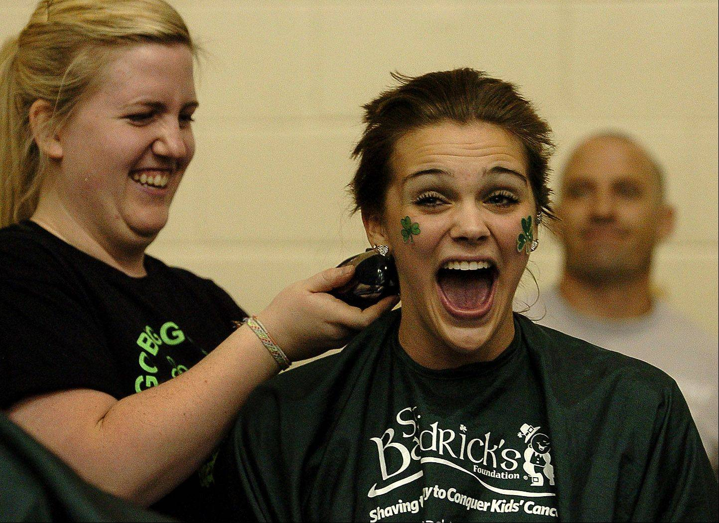 Krystal Vezzetti, who raised $1,293, gets her head shaved by Sarah Hoth of the Hair Cuttery, during the St. Baldrick's head shaving event at Schaumburg High School Thursday.