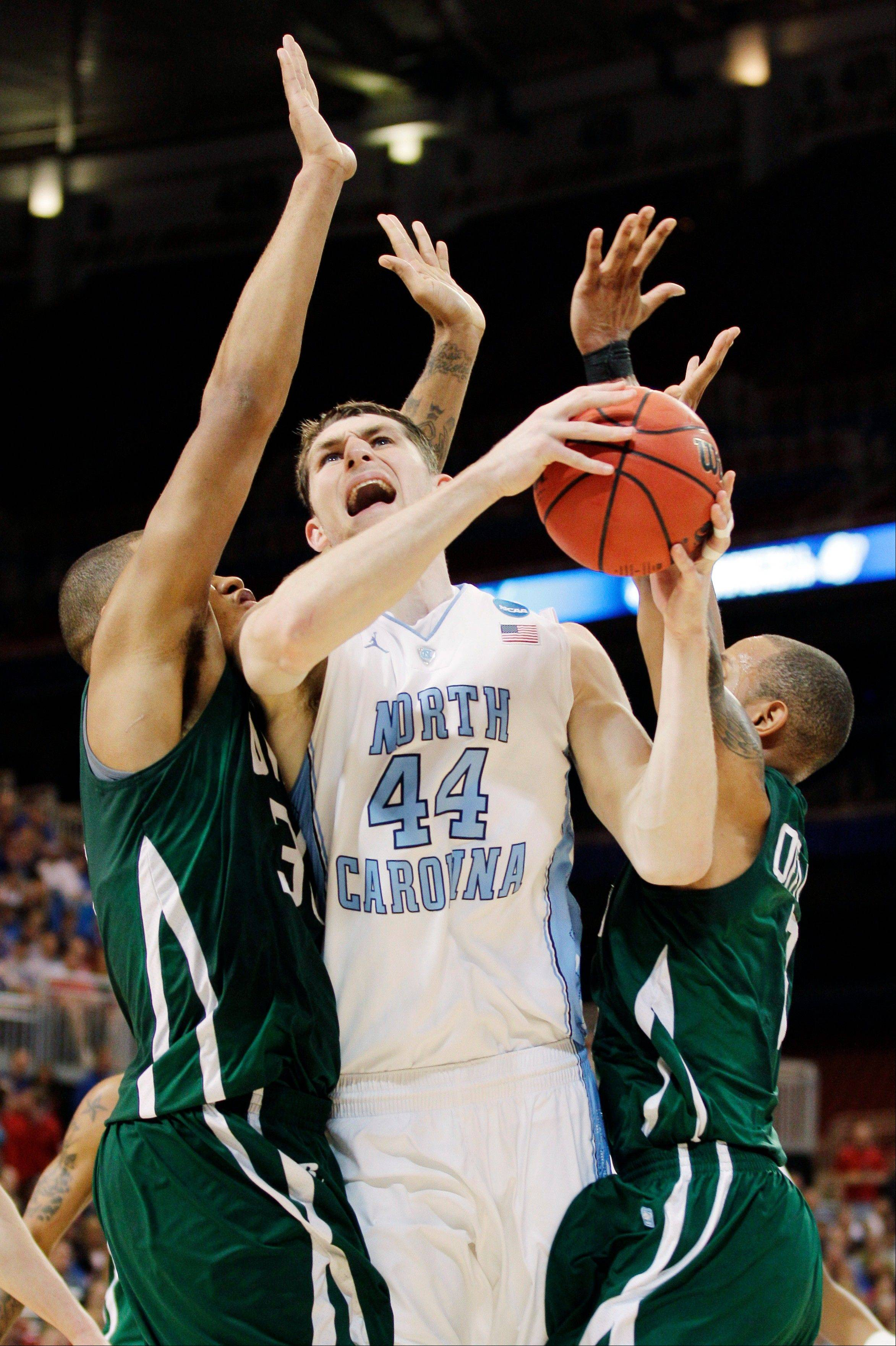 North Carolina forward Tyler Zeller goes up for a shot against Ohio forward Reggie Keely, left, and guard Walter Offutt Friday night in NCAA tournament action.