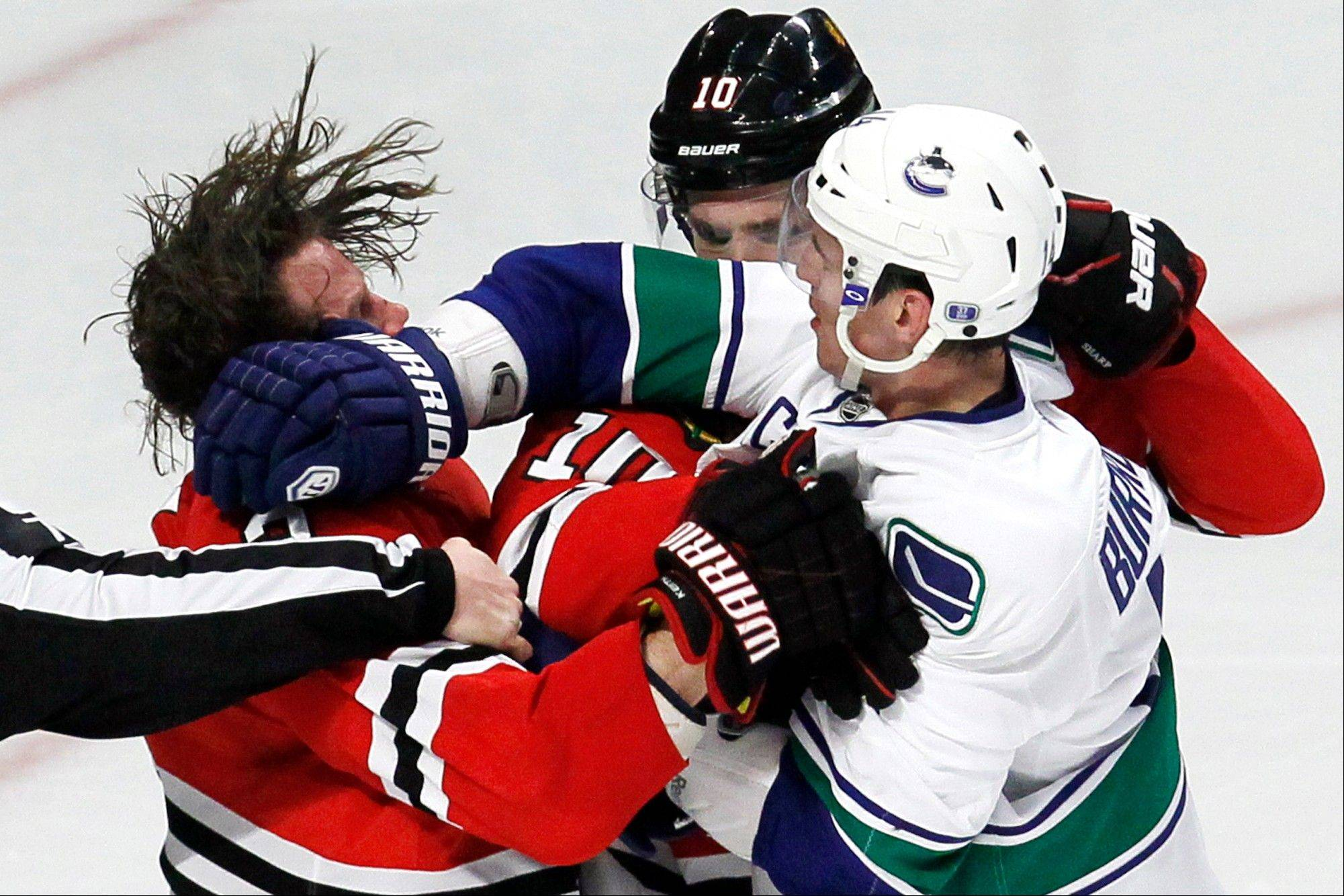 Vancouver's Alex Burrows hits Duncan Keith, left, in the face as Patrick Sharp tries to break them apart Wednesday at the United Center. On Friday, the NHL suspended Keith five games for a hit on the Canucks' Daniel Sedin.