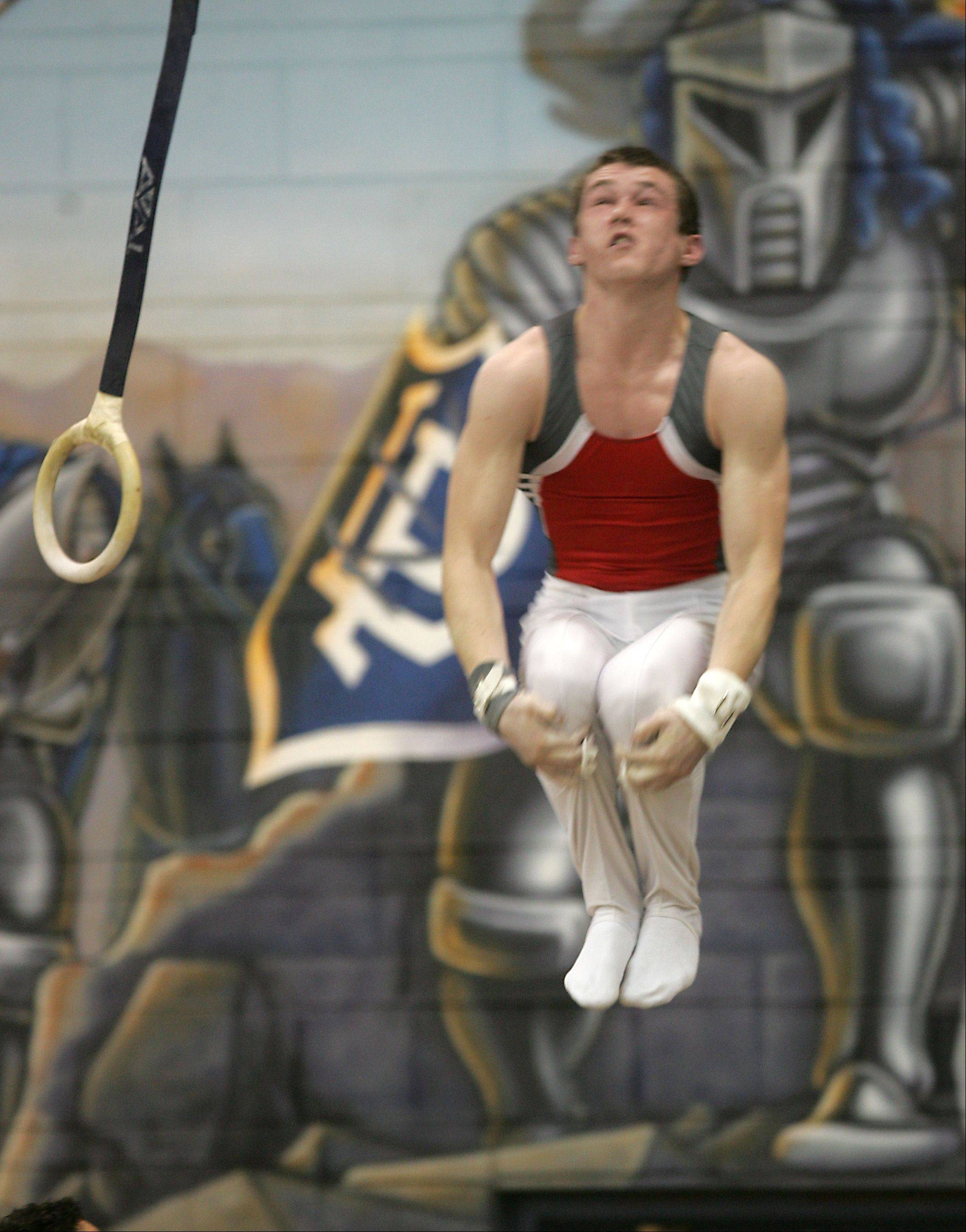 Mundelein's Cameron Mueller dismounts from his still rings routine, during the Ralph Krupke Boys Gymnastics Invitational at Lake Park East High School.
