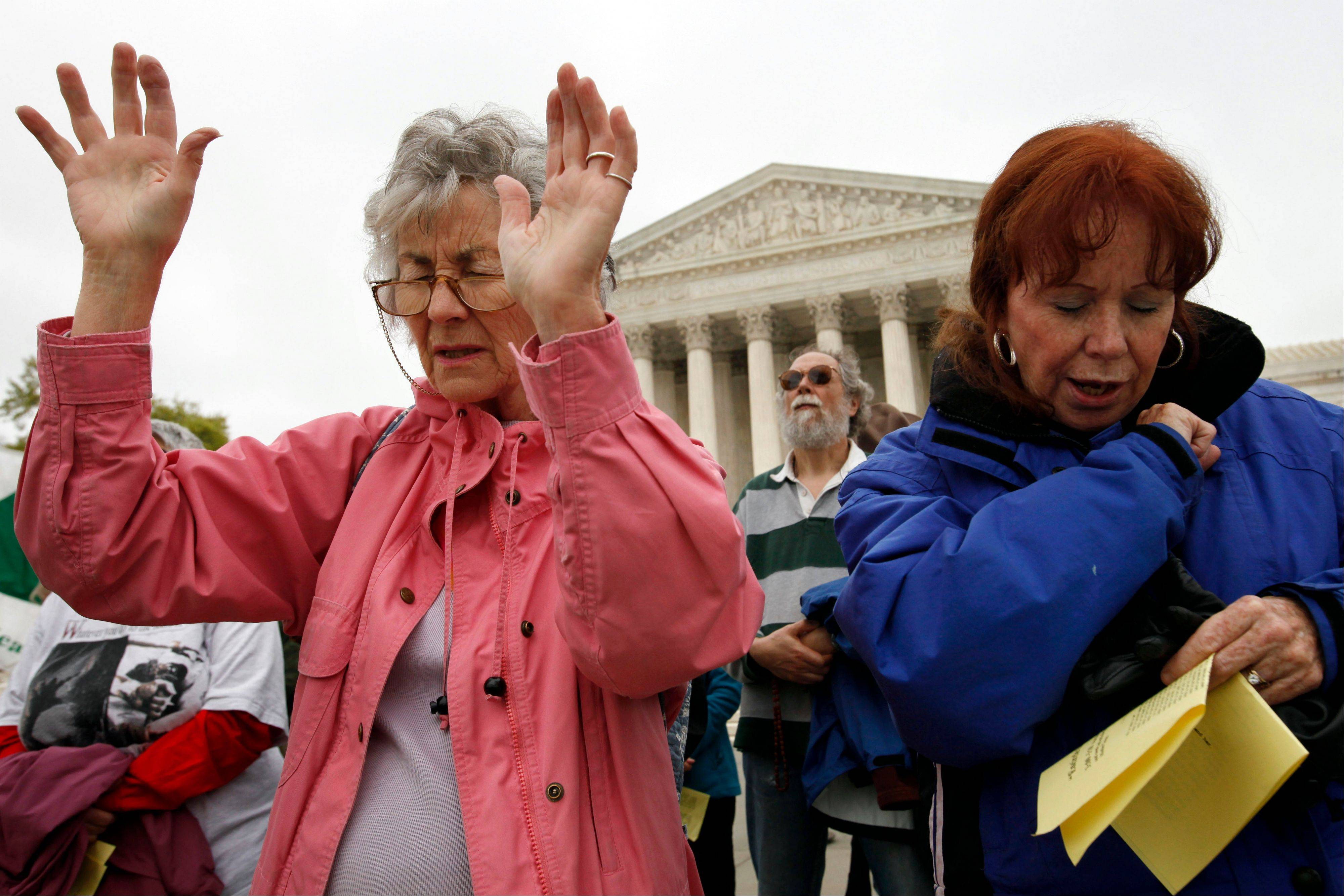 "Joan Schnabel of Annapolis, Md., left, and Marge Groetsch of Front Royal, Va., pray in front of the Supreme Court as part of ""Encircle the Court in Prayer,"" an event led by Christian faith organizations on the eve of the Supreme Court arguments on President Obama's health care legislation, in Washington on Sunday."