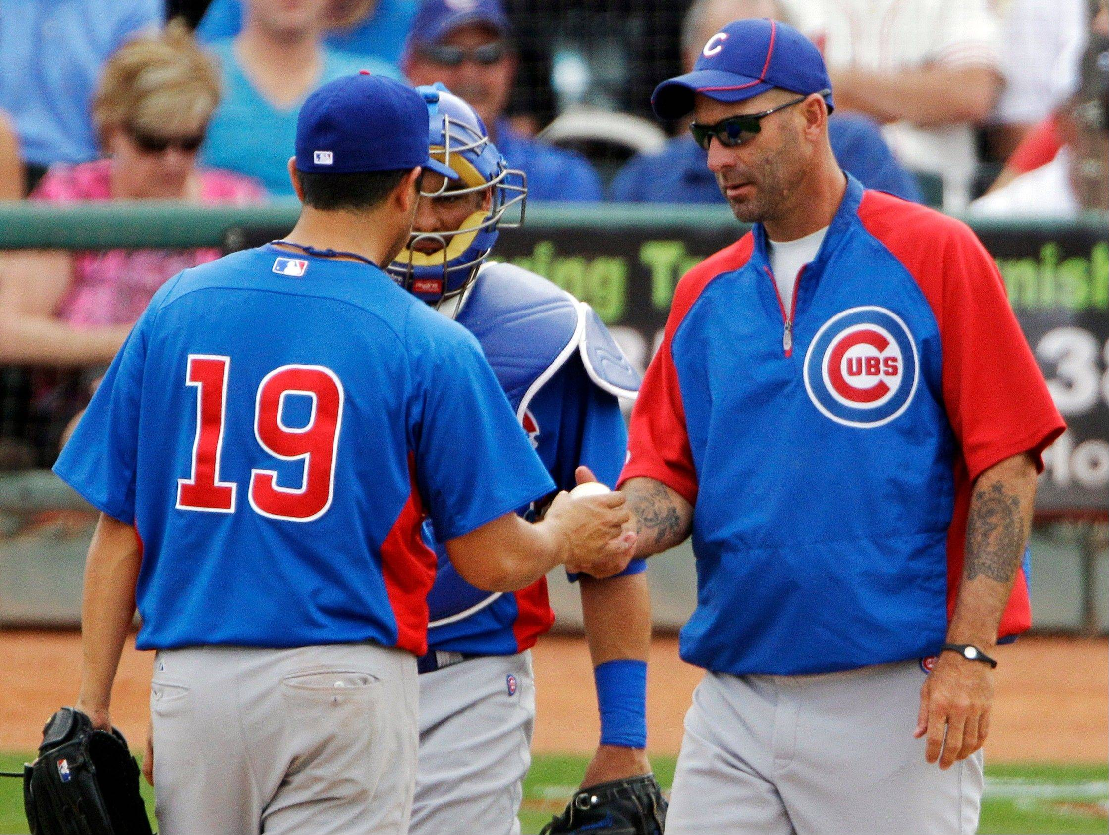 Chicago Cubs manager Dale Sveum, right, takes the ball from starting pitcher Rodrigo Lopez (19) in the fifth inning of a spring training baseball game Sunday against the Cleveland Indians in Goodyear, Ariz.