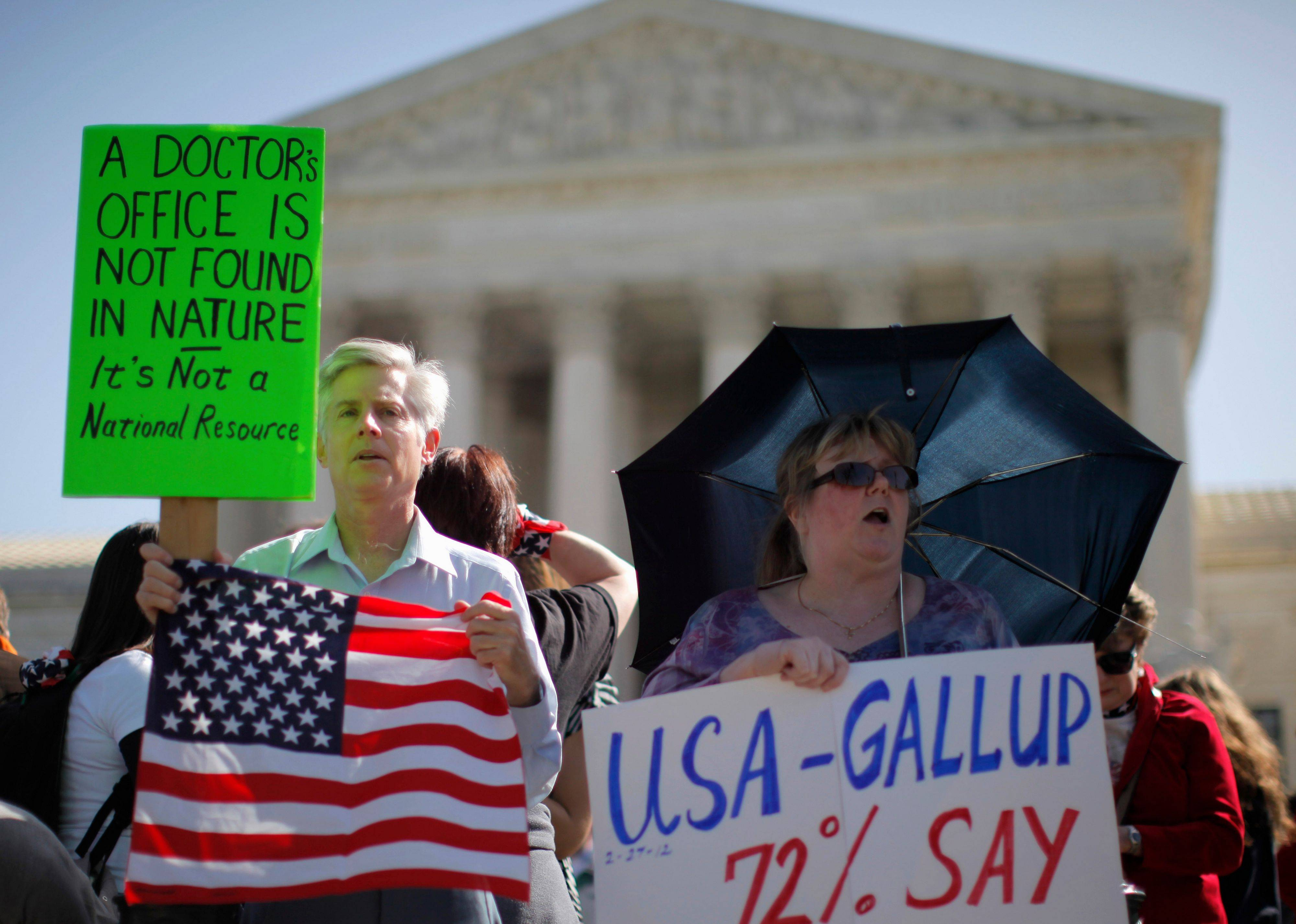David Hayes, from Washington and Maureen Murphy from Madison, Miss., who oppose the health care reform law, rally in front of the Supreme Court Monday, as the court began three days of arguments on health care. presidential candidate, former Pennsylvania Sen. Rick Santorum, lower right.