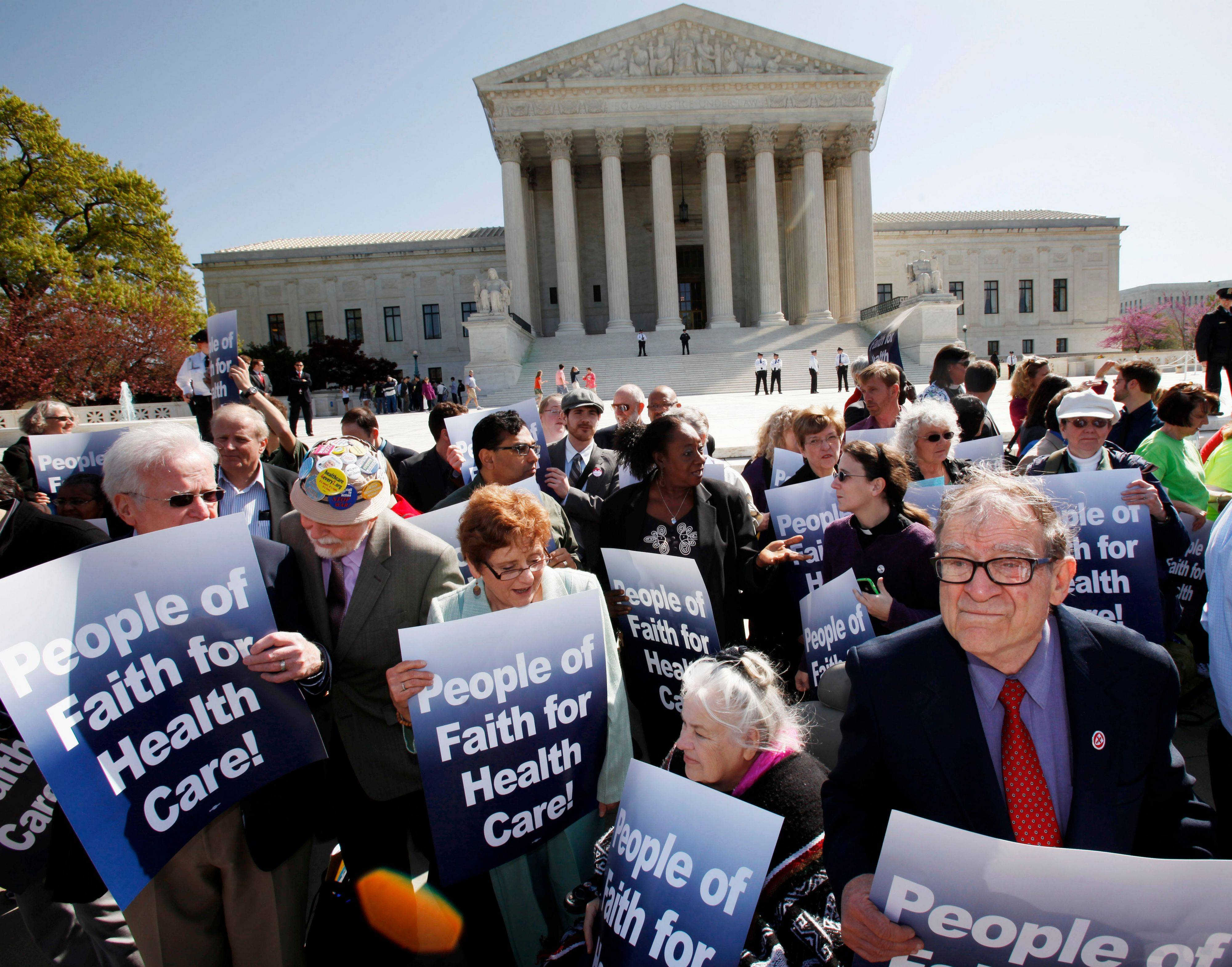 Protesters in favor of health care reform demonstrate outside of the Supreme Court in Washington, Monday, as a hearing on President Obama's health care legislation began.