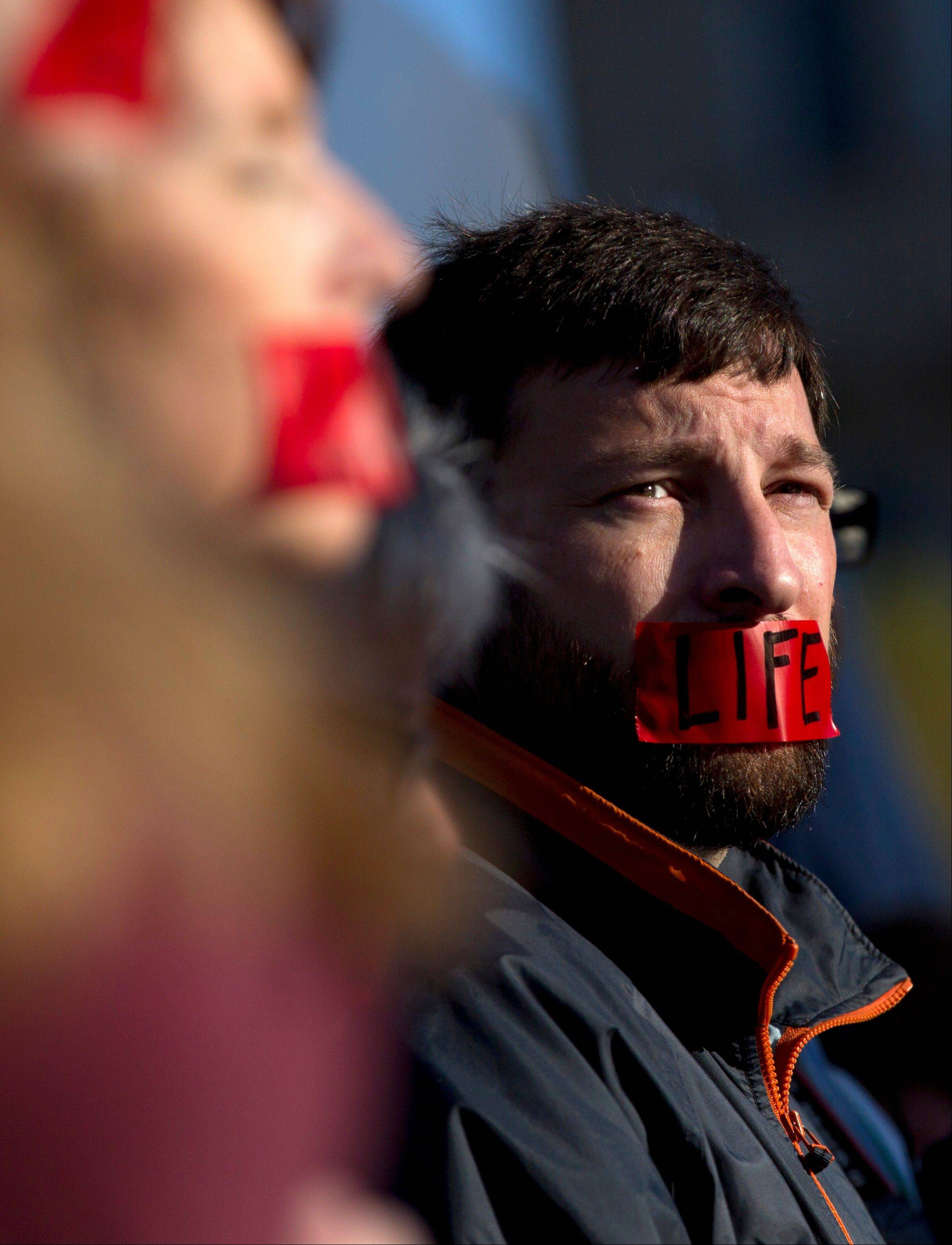 "A member of ""Bound 4 Life"" protests outside the Supreme Court in Washington, Monday, March 26, 2012, as the court began hearing arguments on the constitutionality of President Barack Obama's health care overhaul."